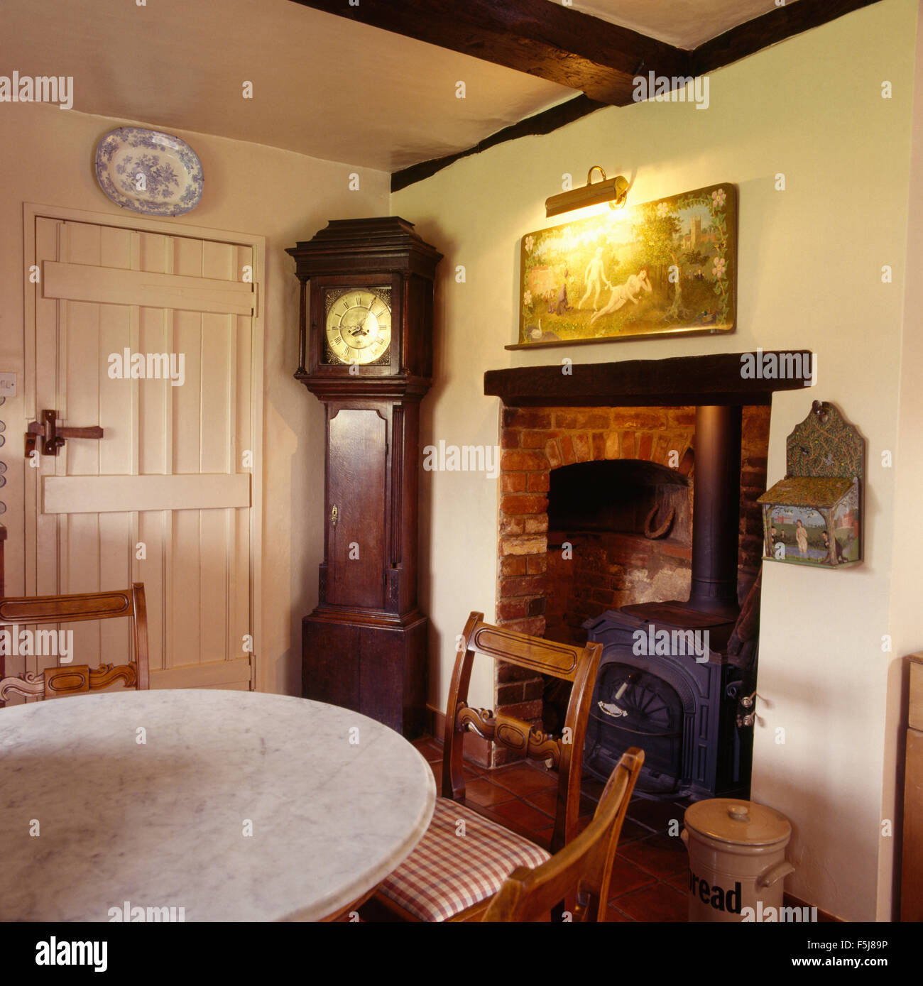 Antique long case clock in corner of traditional an eighties cottage dining room with a wood burning stove in a Stock Photo