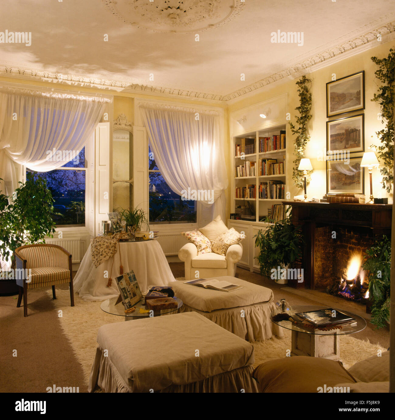 White voile drapes on windows in eighties apartment living room with lighted fire in fireplace - Stock Image