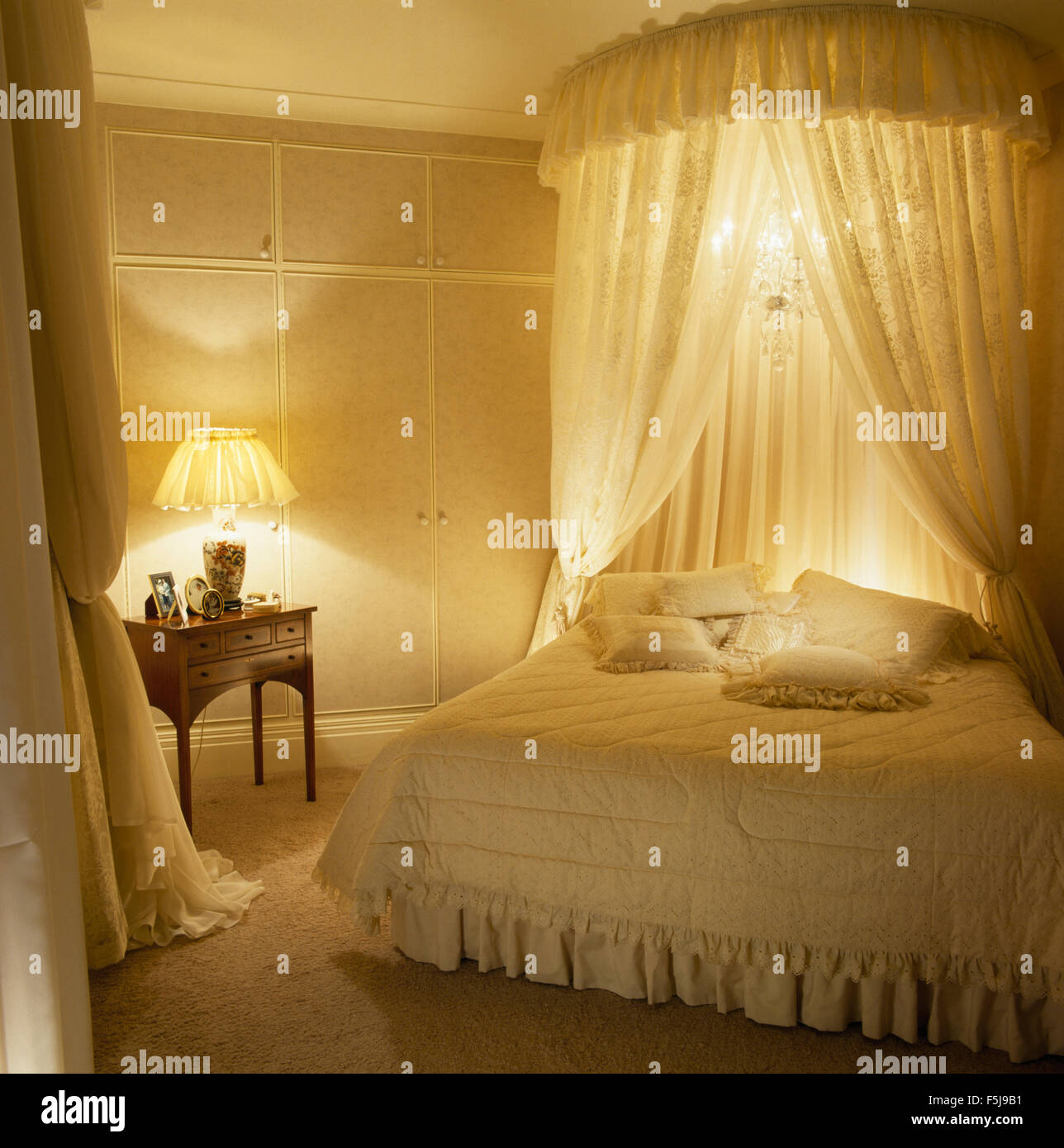 Coronet With Lace Curtains And Small Chandelier Above Bed