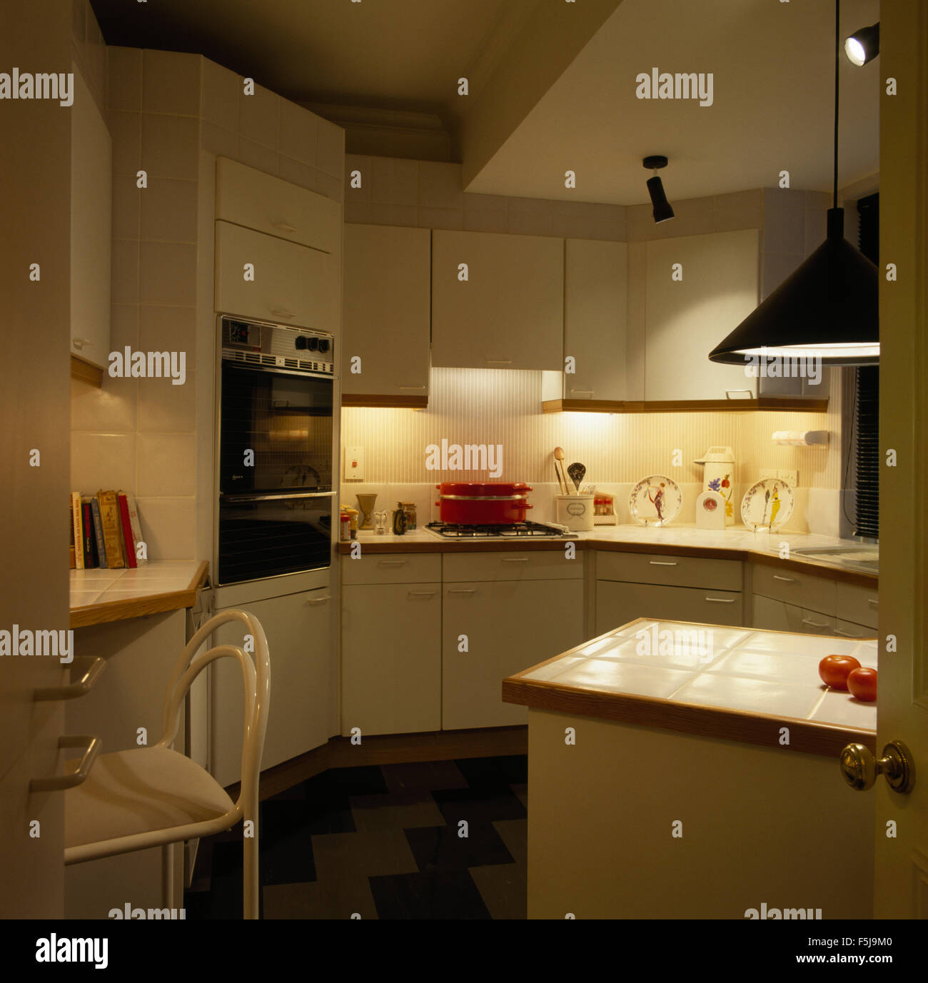 Seventies kitchen with recessed lighting below fitted cupboards - Stock Image