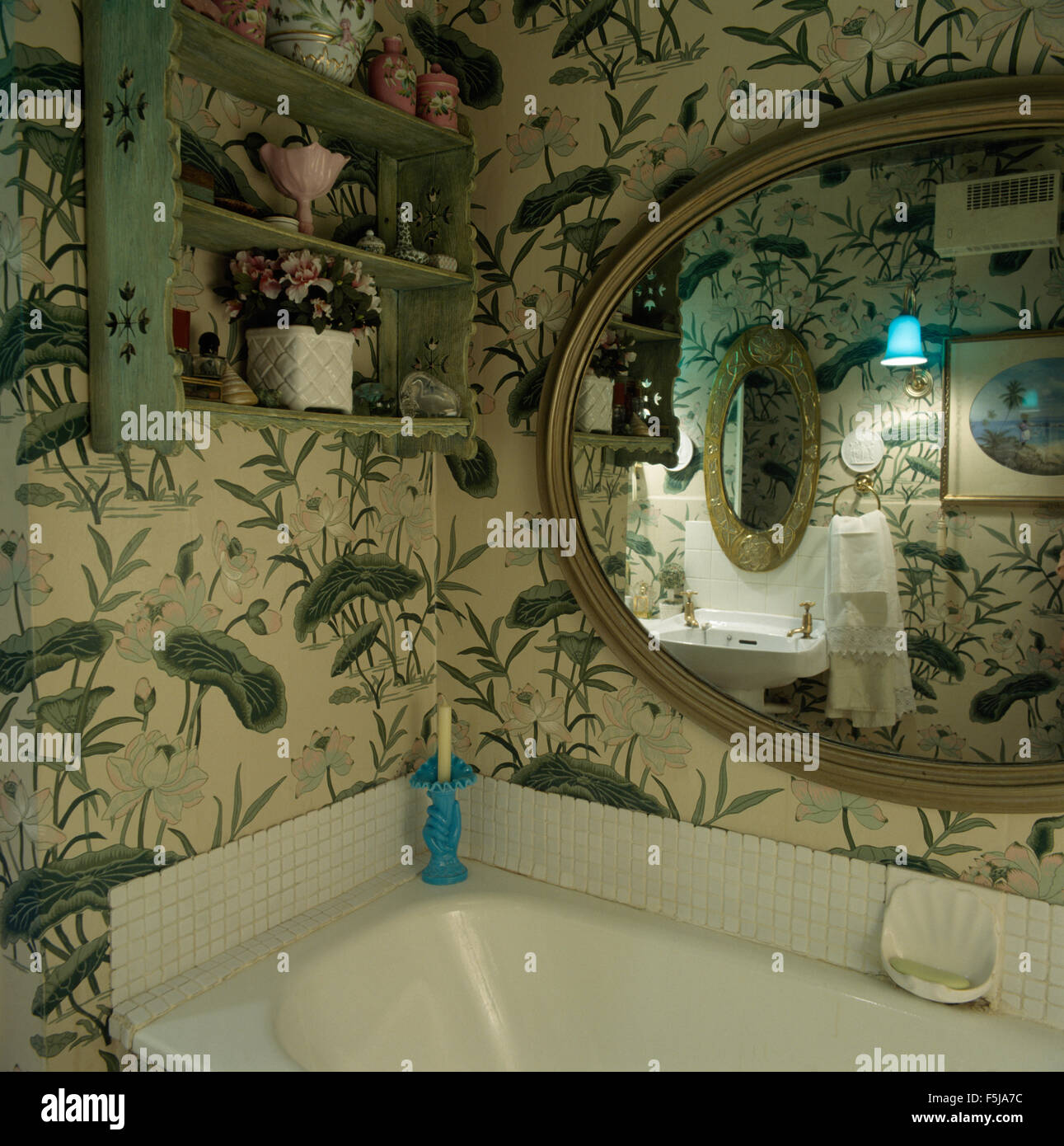 Painted wooden shelves and large oval mirror above the bath in an eighties bathroom with large patterned foliage - Stock Image