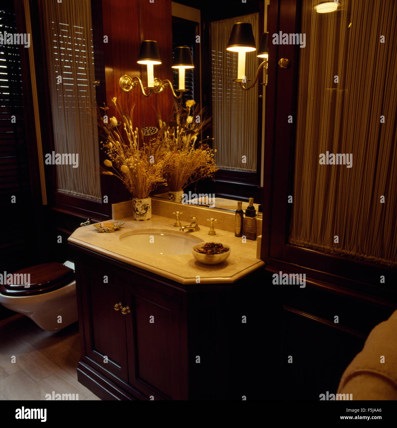 Wall lights either side of mirror above a mahogany vanity unit in a dark eighties bathroom - Stock Image