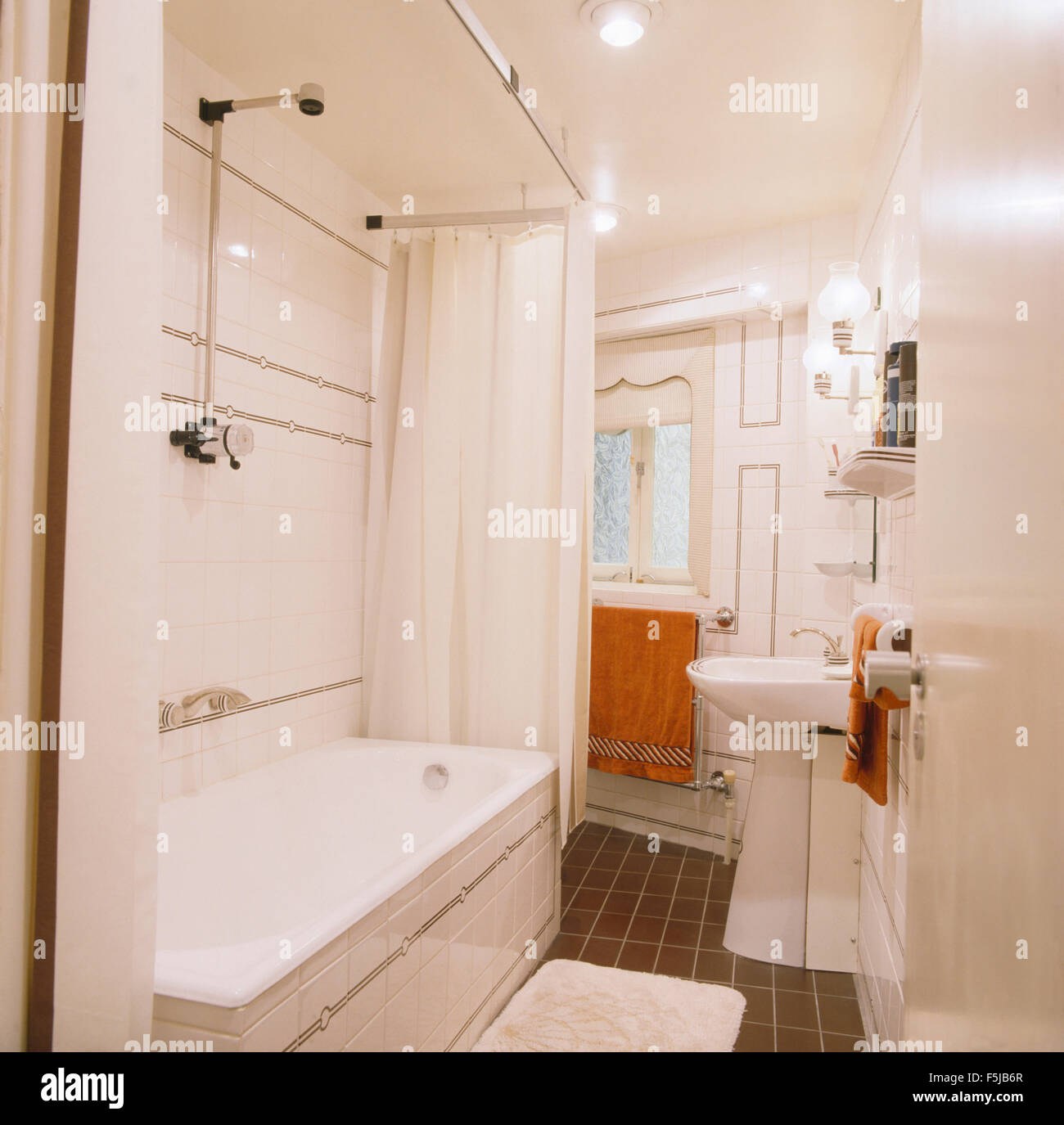 Chrome shower above bath in white shower curtains in a white ...