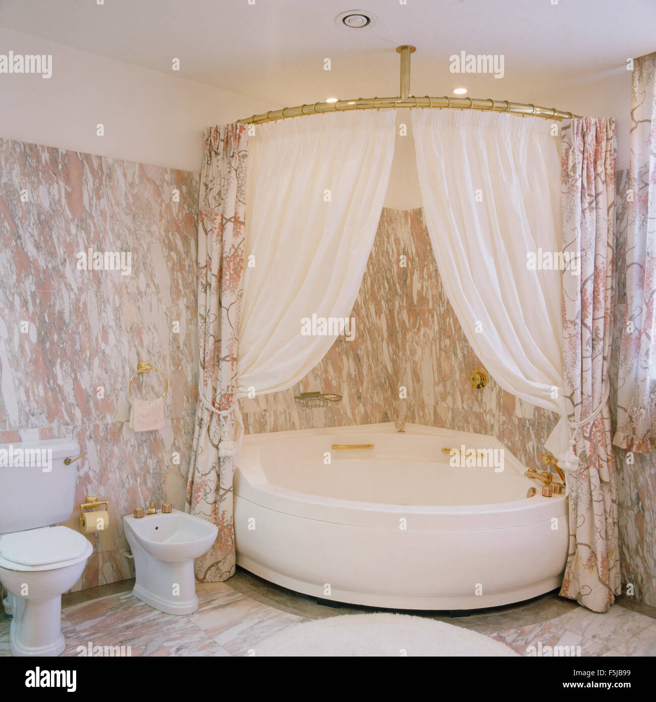 White Shower Curtains On Corner Bath In An Eighties Marble Bathroom