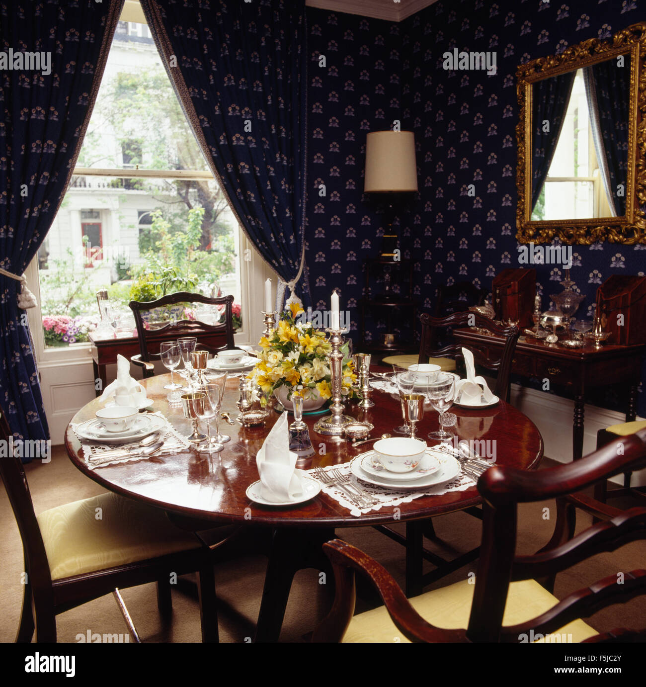 Dark blue wallpaper and matching curtains in eighties dining room with table set for lunch - Stock Image
