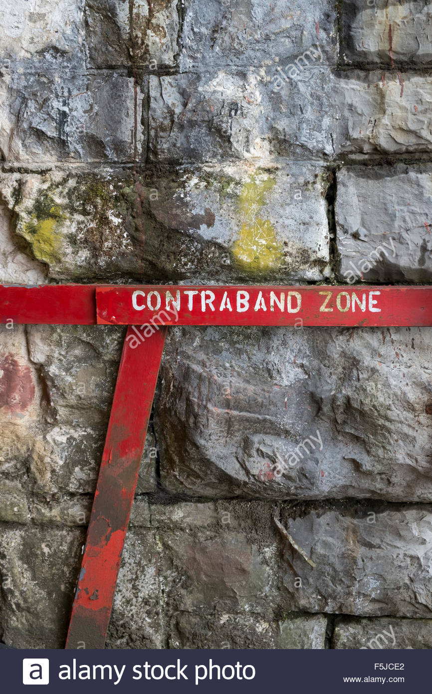 Contraband Zone sign against a rough stone wall - Stock Image