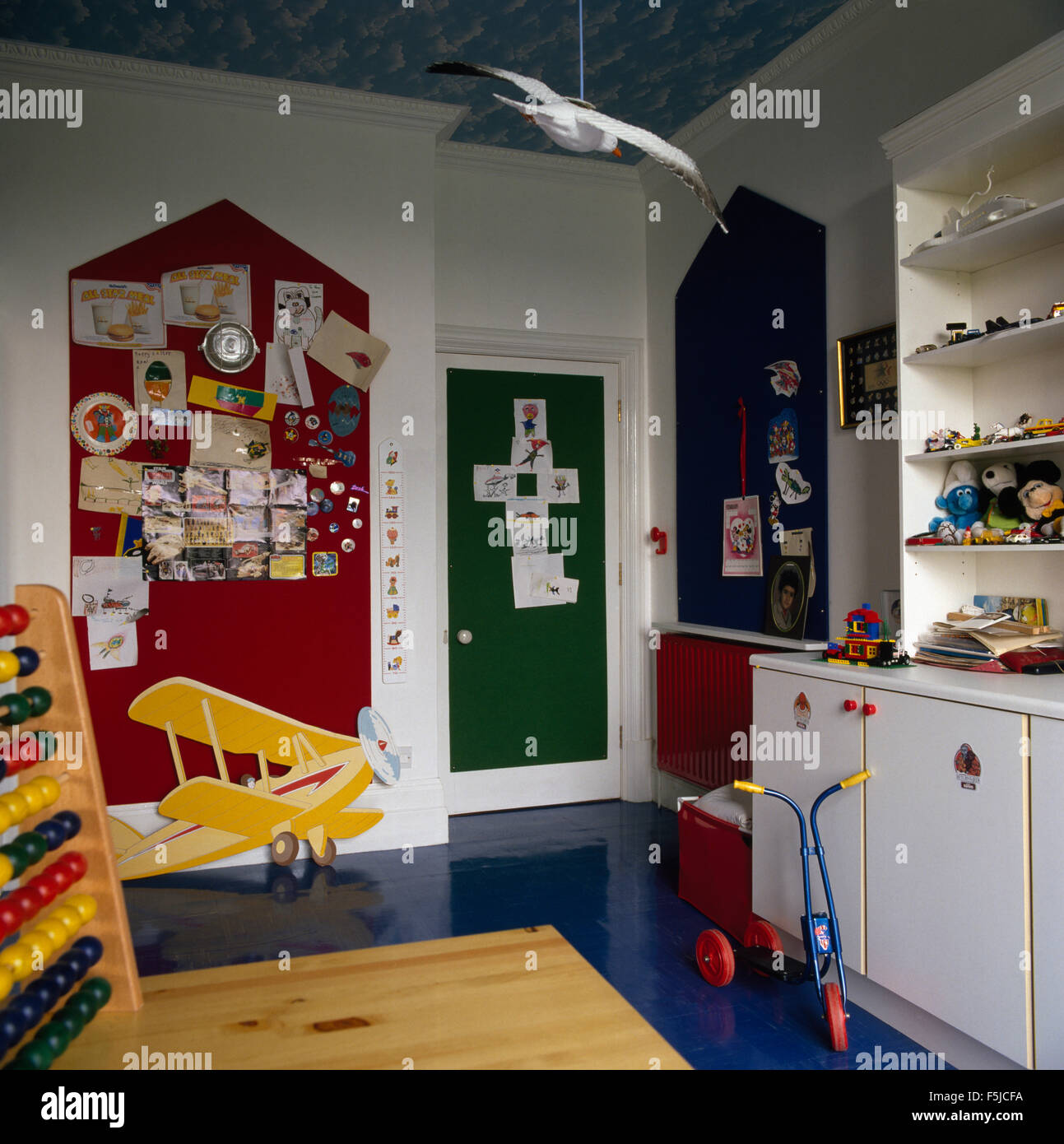 Scooter and toy bi-plane in children's eighties playroom - Stock Image