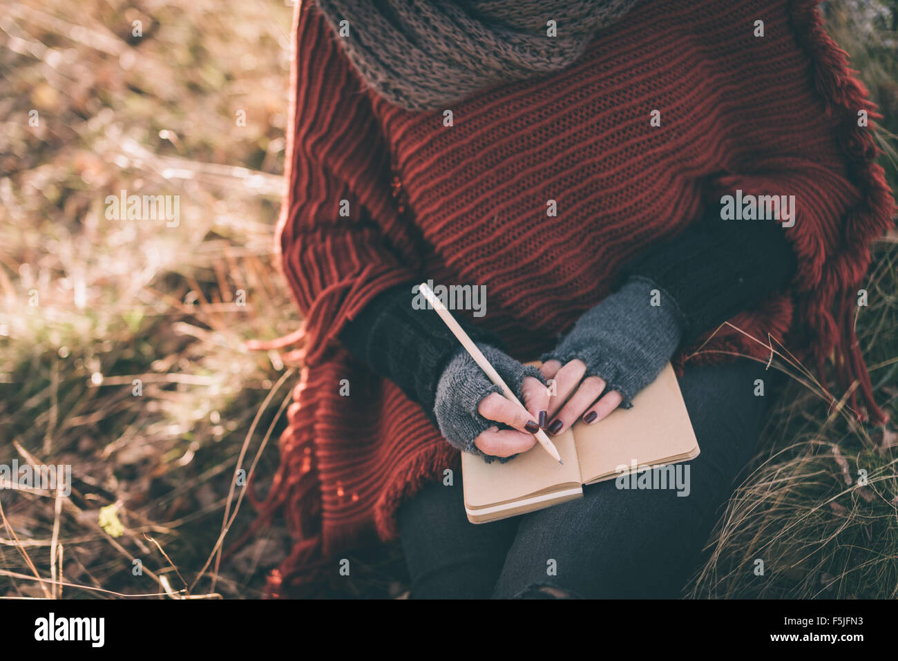 Woman writing in the notebook - Stock Image