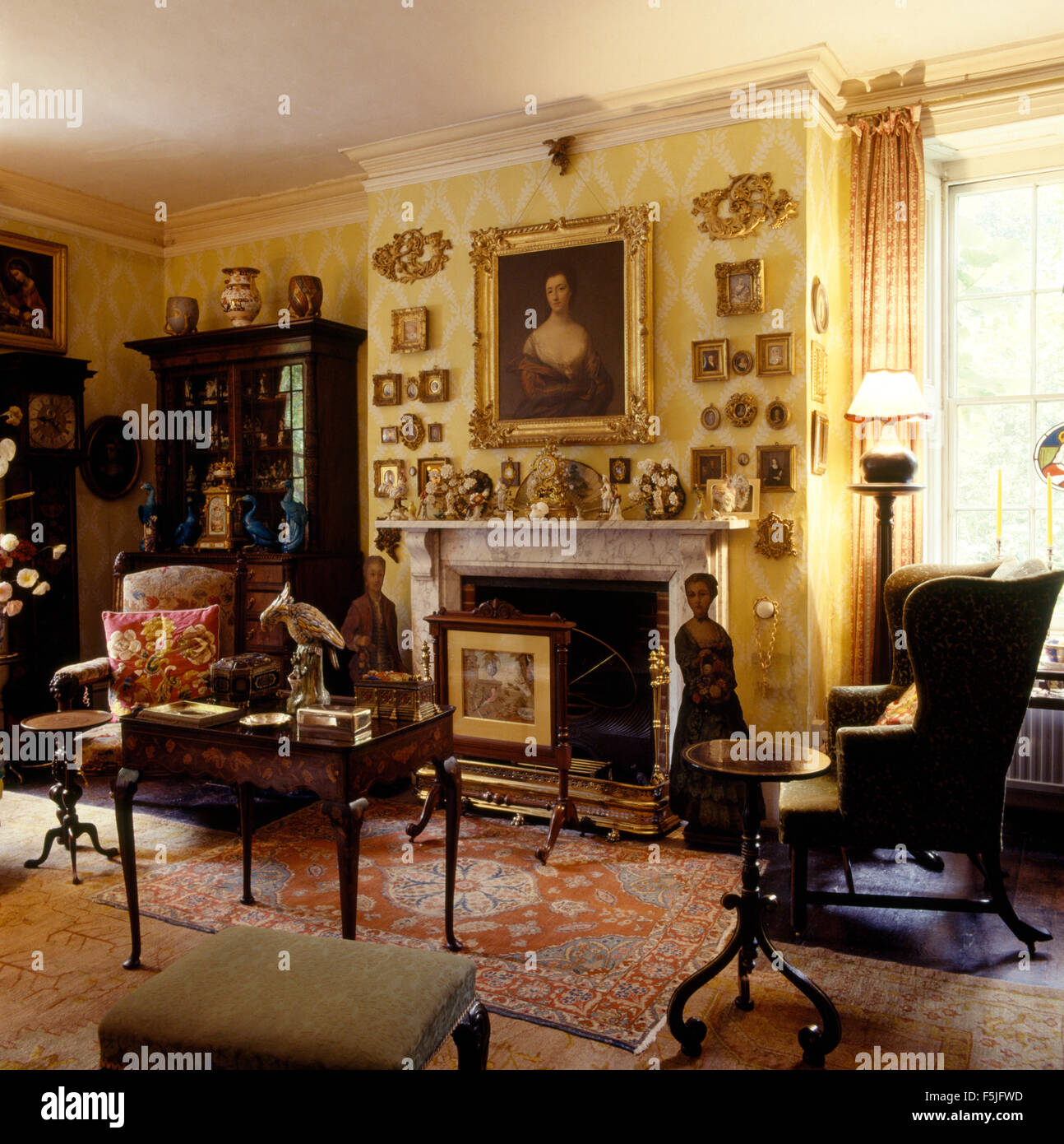 Gilt framed miniatures on wall above fireplace in drawing room of a Jacobean rectory with antique furniture Stock Photo
