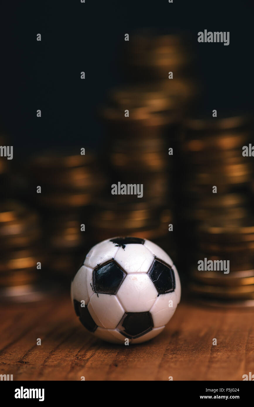 Soccer bet concept with small football on top of coin stack, making money by predicting sport results. - Stock Image