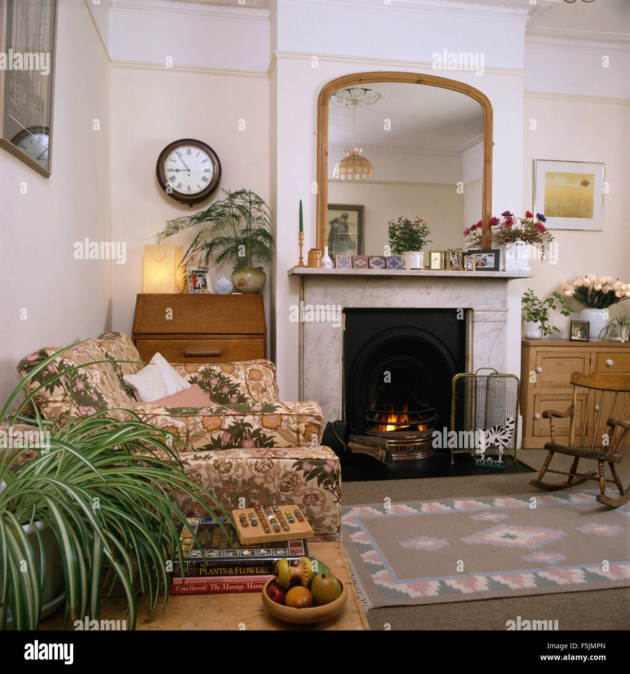 Mirror Above Marble Fireplace With Lighted Fire In Nineties
