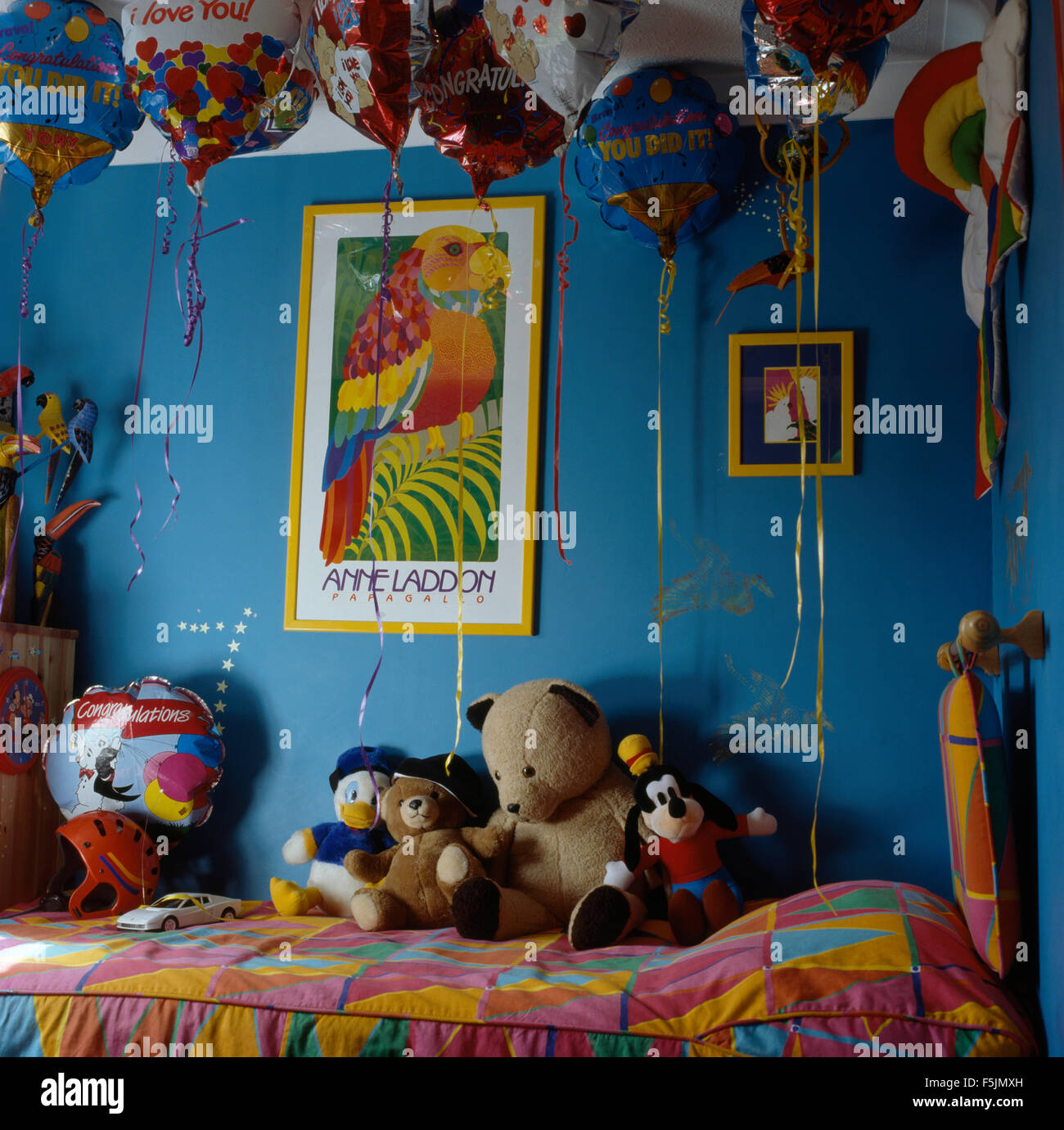 balloons above bed with soft toys in a child s blue nineties bedroom