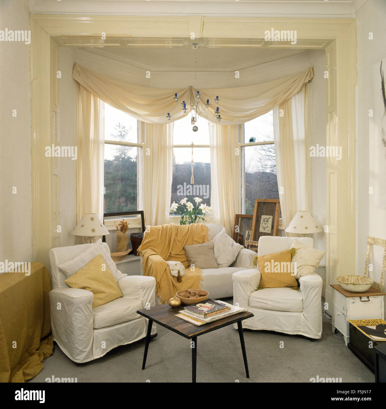 White Swagged Voile Curtains On Bay Window In A Nineties Living Room