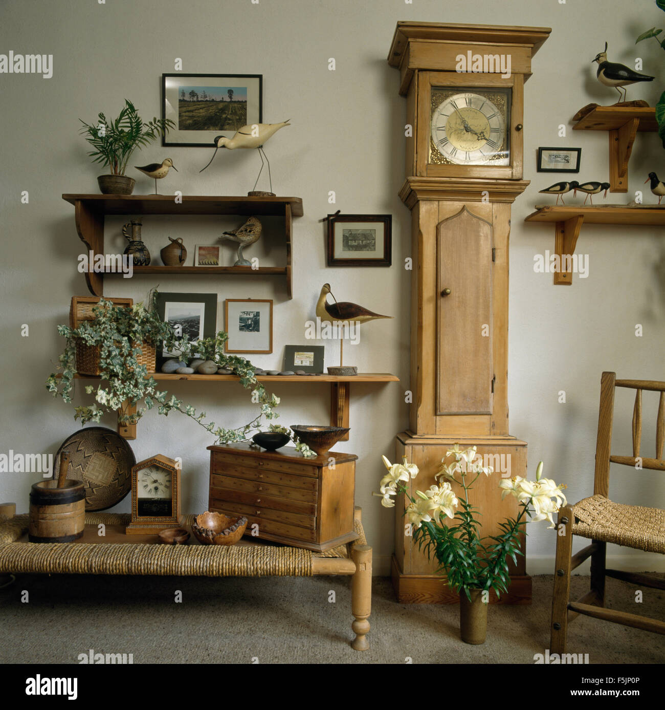 Pine long case clock and a low rattan stool in a nineties dining room with collection of wooden birds on small shelves - Stock Image
