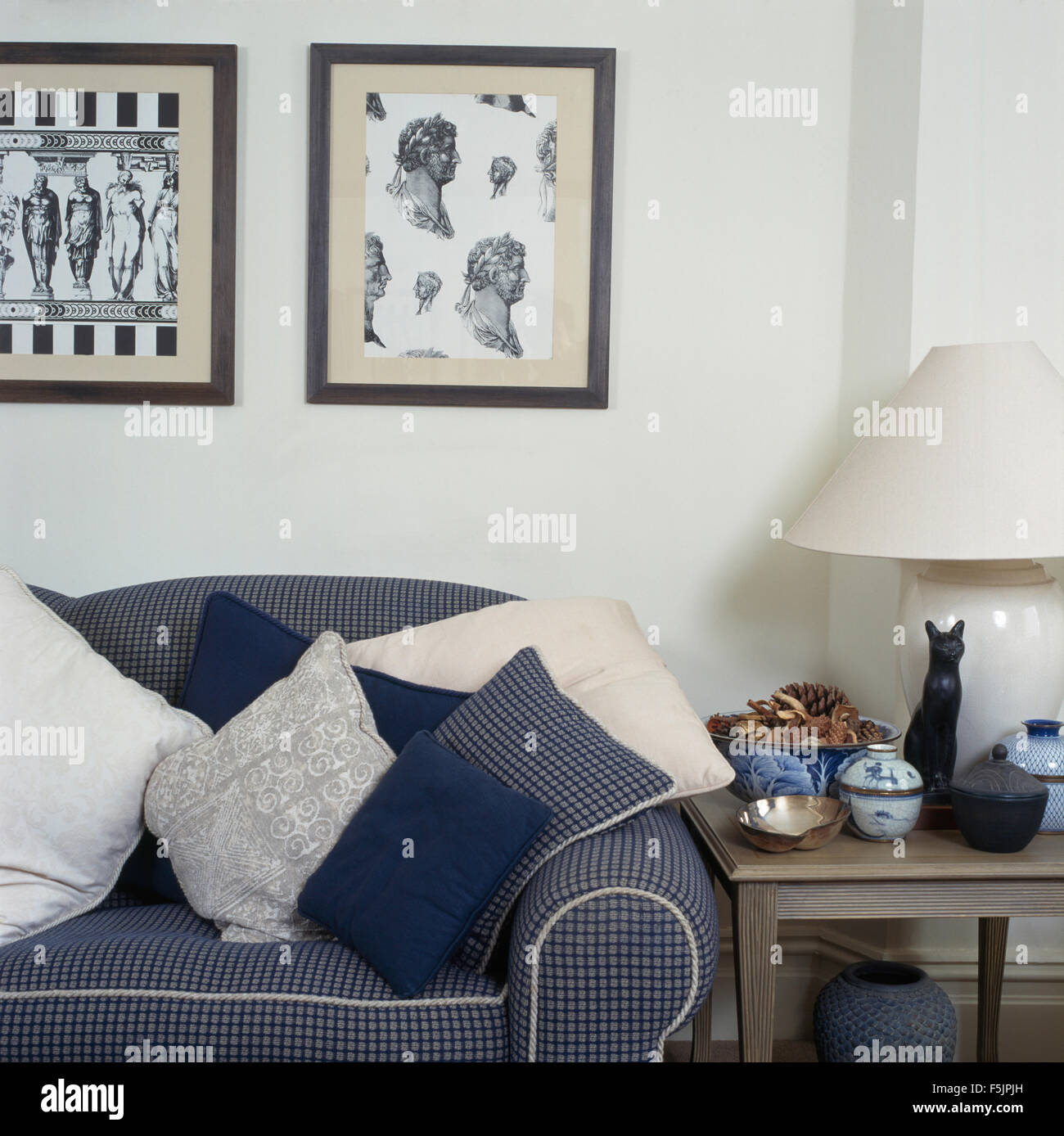 Black+white neo-classical framed prints above a blue checked sofa ...