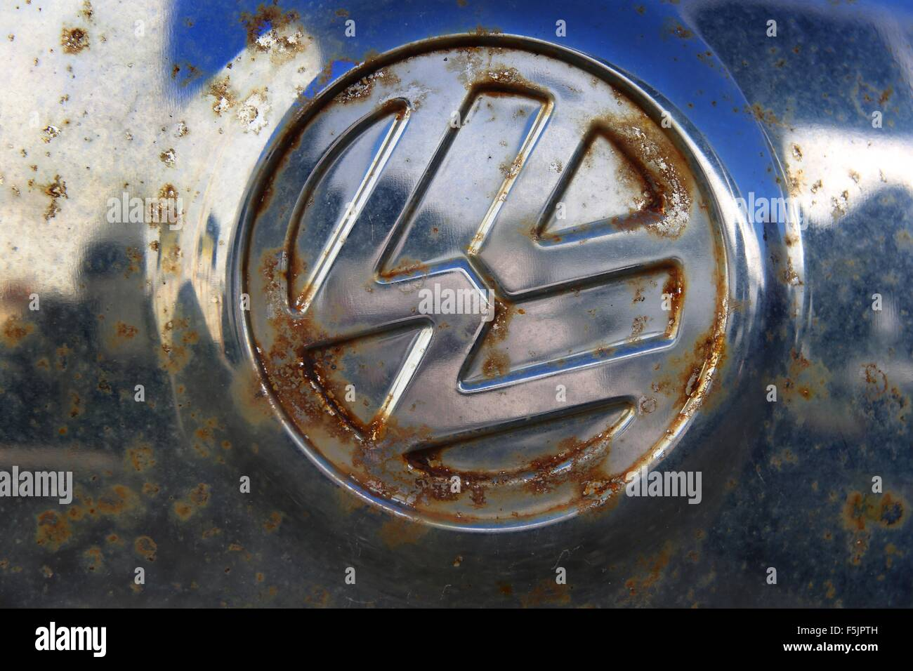 A Rusty Vw Logo On The Hubcap Of An Old Vw Beetle At A Garage In