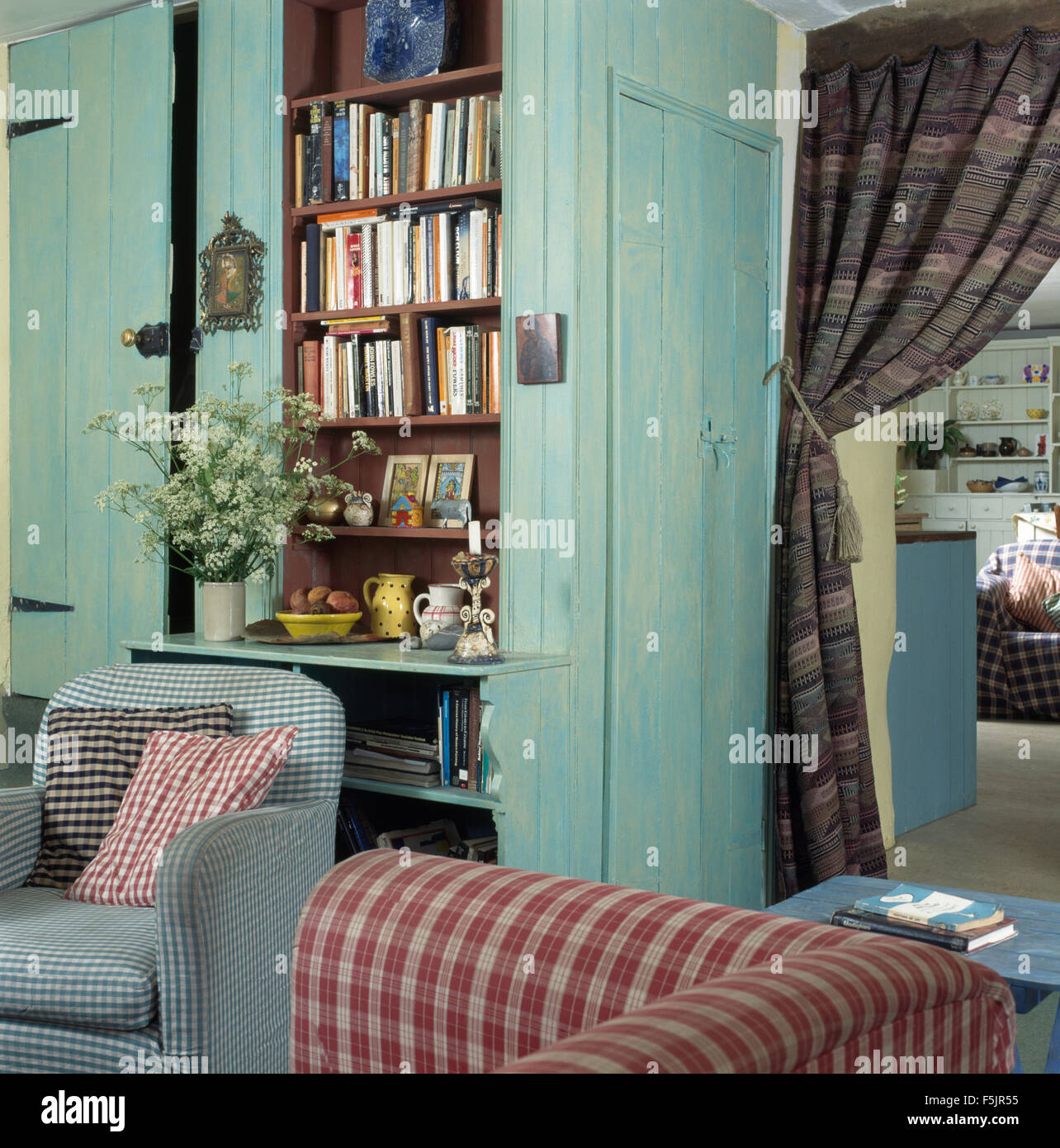 Checked Armchair And Sofa In A Cottage Living Room With Pale Turquoise  Painted Paneling And Fitted Bookcase
