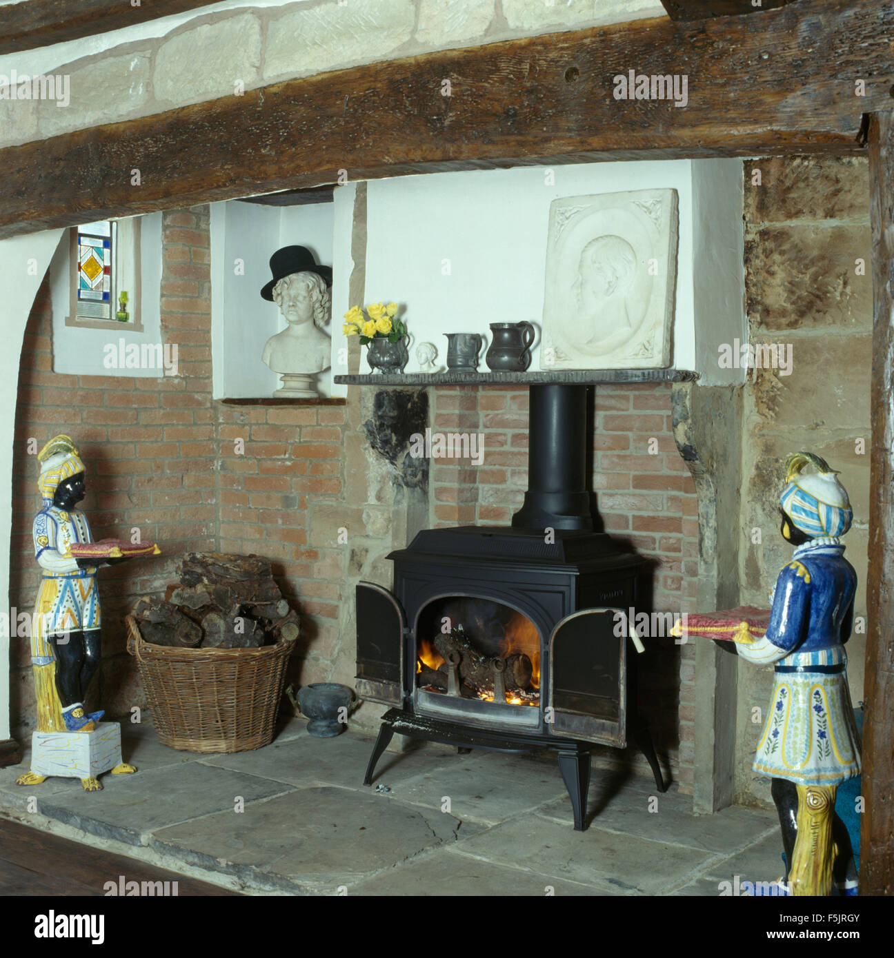 Blackamoor china figures either side of a wood burning stove in an inglenook fireplace - Stock Image
