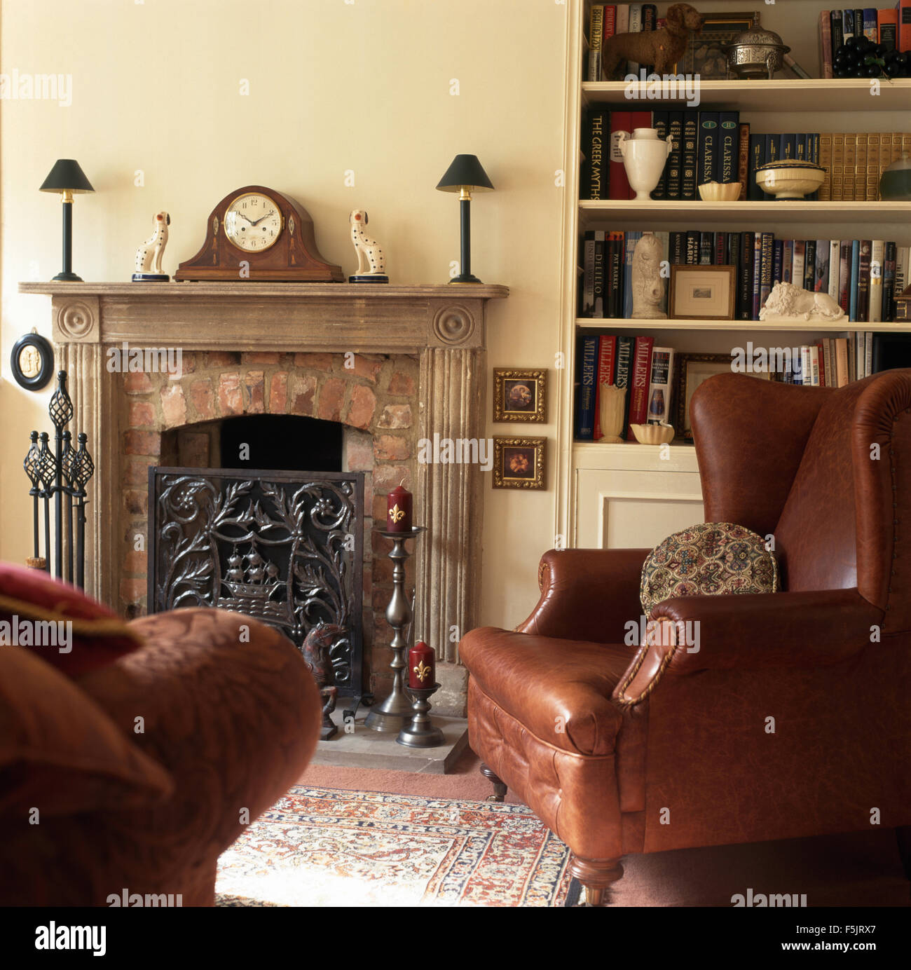 Brown Leather Wing Chair Beside Fireplace With An Ornate Cast Iron Screen  In A Nineties Living Room With Fitted Bookshelves