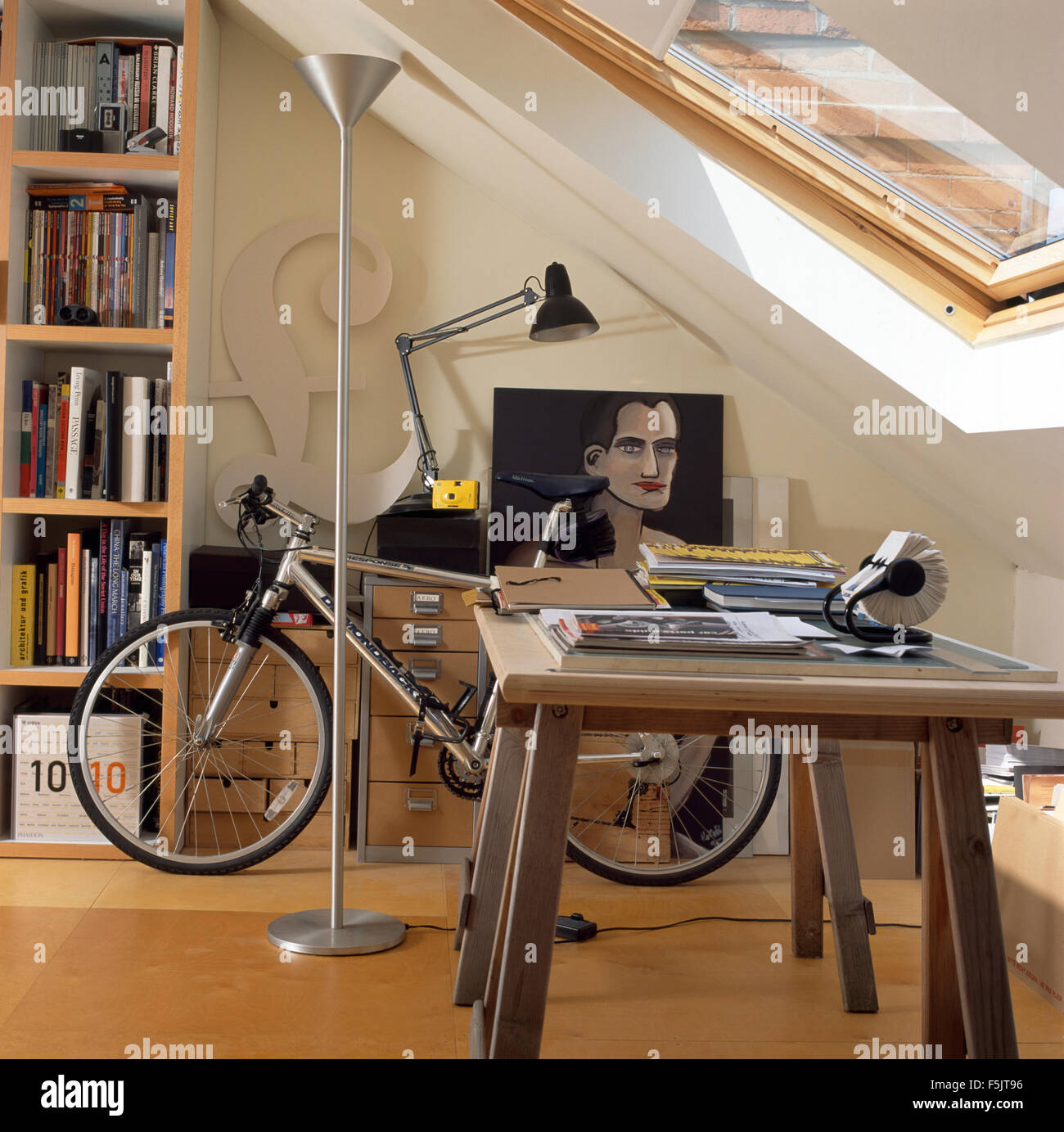 Bicycle and tall chrome floor lamp in attic study - Stock Image