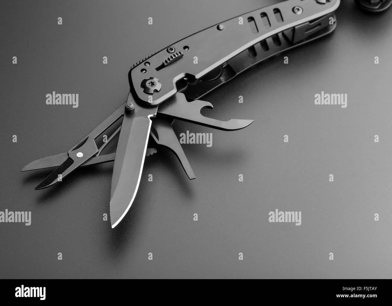 Closeup of black opened multitool knife - Stock Image