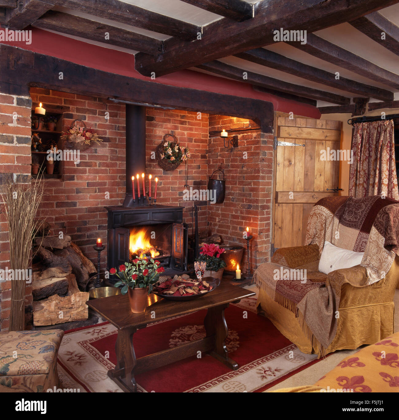 Wood burning stove in inglenook fireplace in  a beamed nineties country living room with an oak coffee table beside - Stock Image