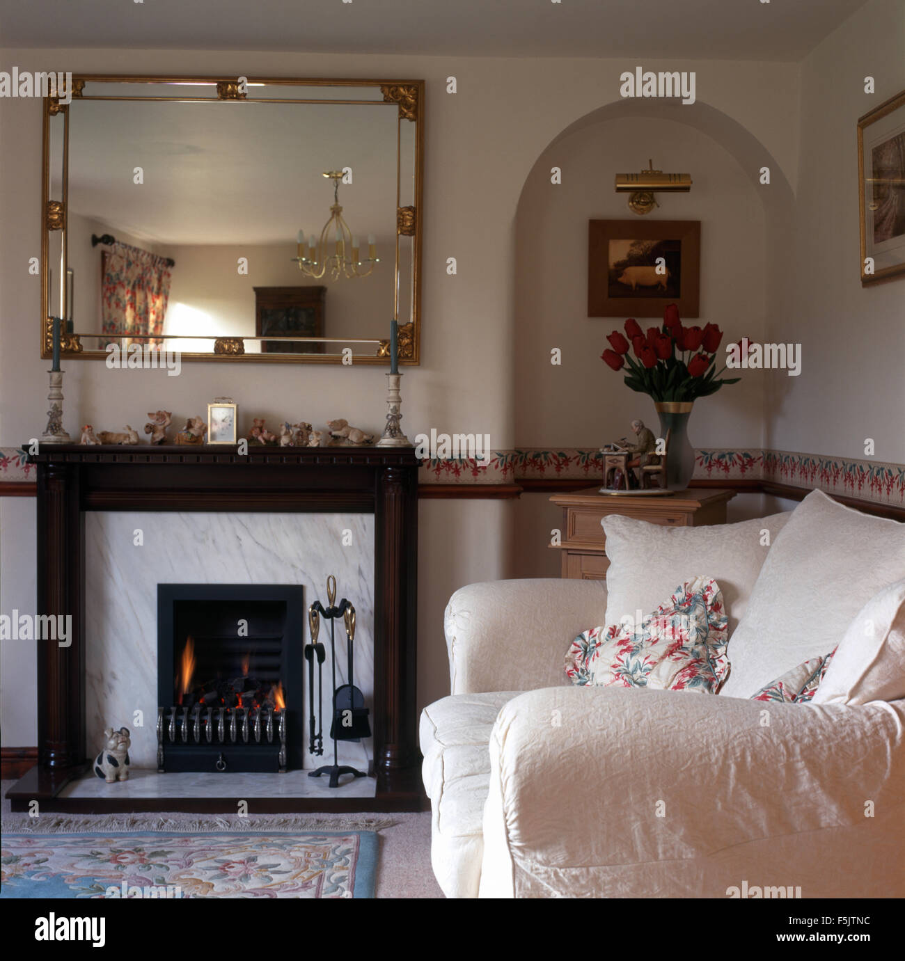 Wonderful Gilt mirror above fireplace with lighted fire in a nineties living  OQ16