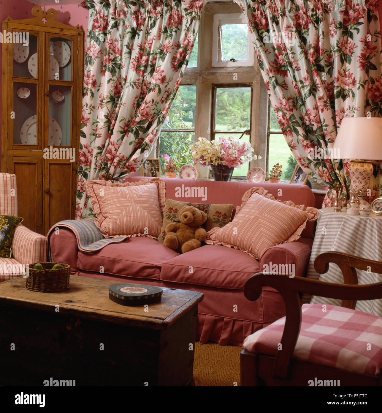 Floral Curtains On Window Behind A Pink Sofa In Country Living Room With An  Old Pine Chest Used As A Coffee Table