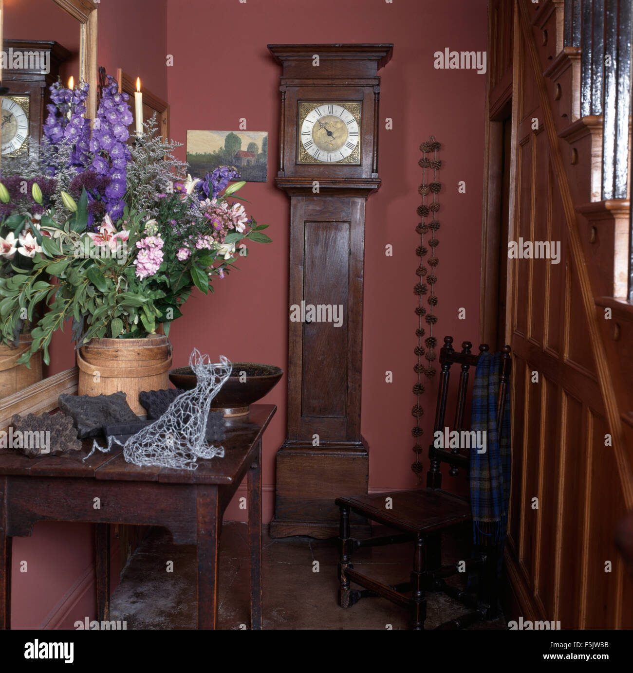 Summer flower arrangement on console table in a nineties pink cottage hall with an antique long case clock and wooden - Stock Image