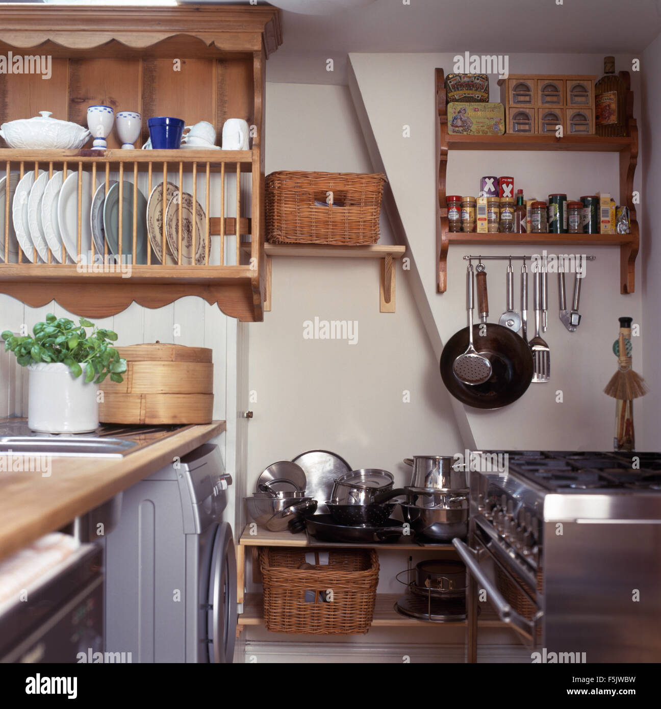 Pine plate rack above worktop in a cottage kitchen with stainless steel pans on rack below wooden shelving & Pine plate rack above worktop in a cottage kitchen with stainless ...