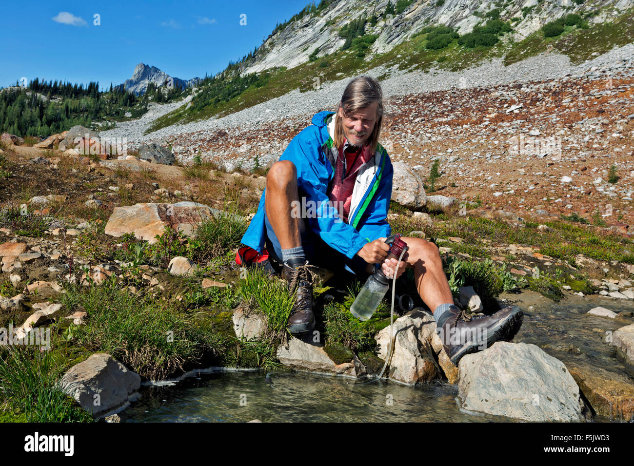 WASHINGTON - Pumping water for drinking from Upper Lyman Lake in the Glacier Peak Wilderness area of the Cascade - Stock Image