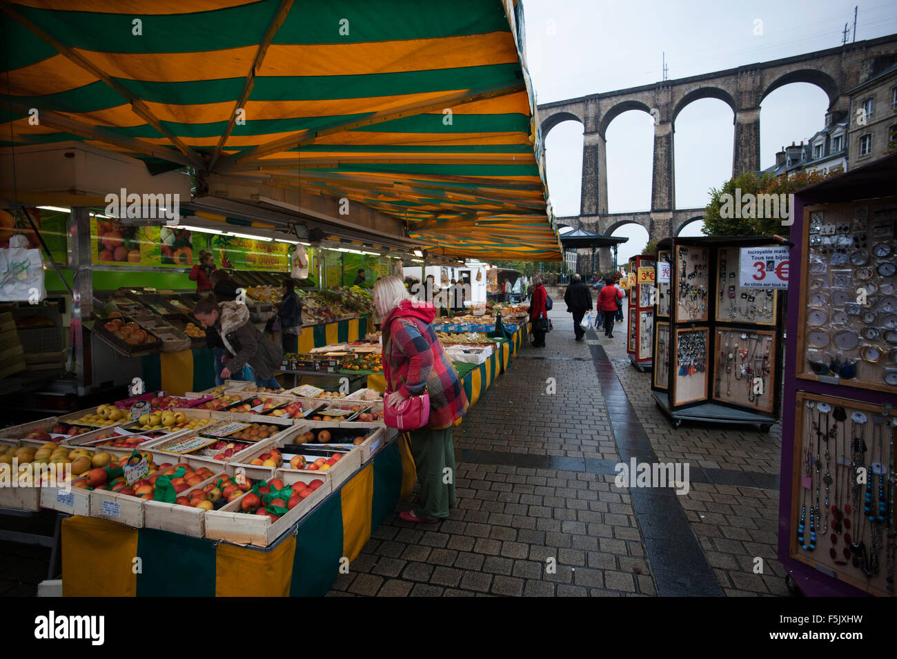Morlaix, Brittany, France. The market and old buildings and Viaduct. October 2015 Woman in red coat model released. - Stock Image
