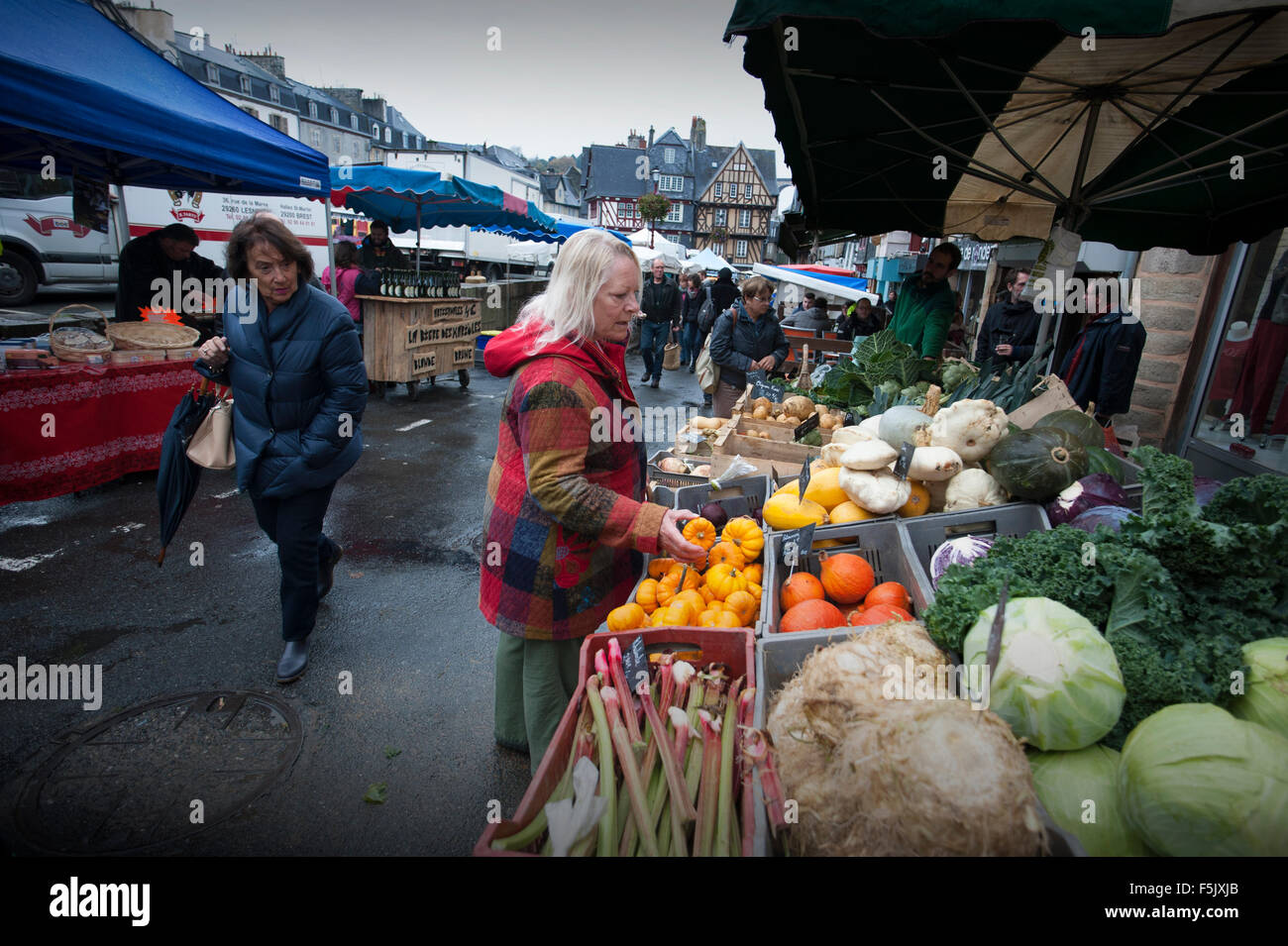 Morlaix, Brittany, France. The market and old buildings. October 2015 Woman in red coat model released. - Stock Image