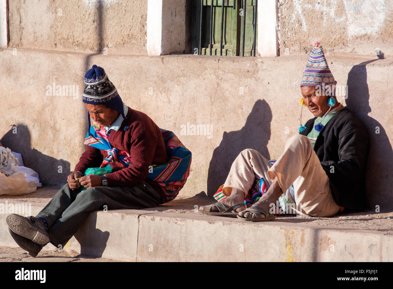 Typically dressed men with Chullos, chewing coca at siesta, Colquechaca, Potosi, Bolivia - Stock Image