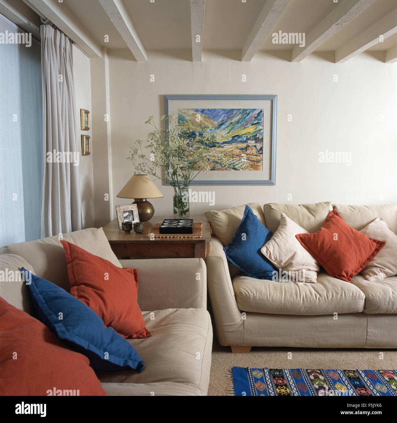 Blue And Red Cushions On Cream Sofas In A Traditional Living Room With A  Lime Washed Beamed Ceiling