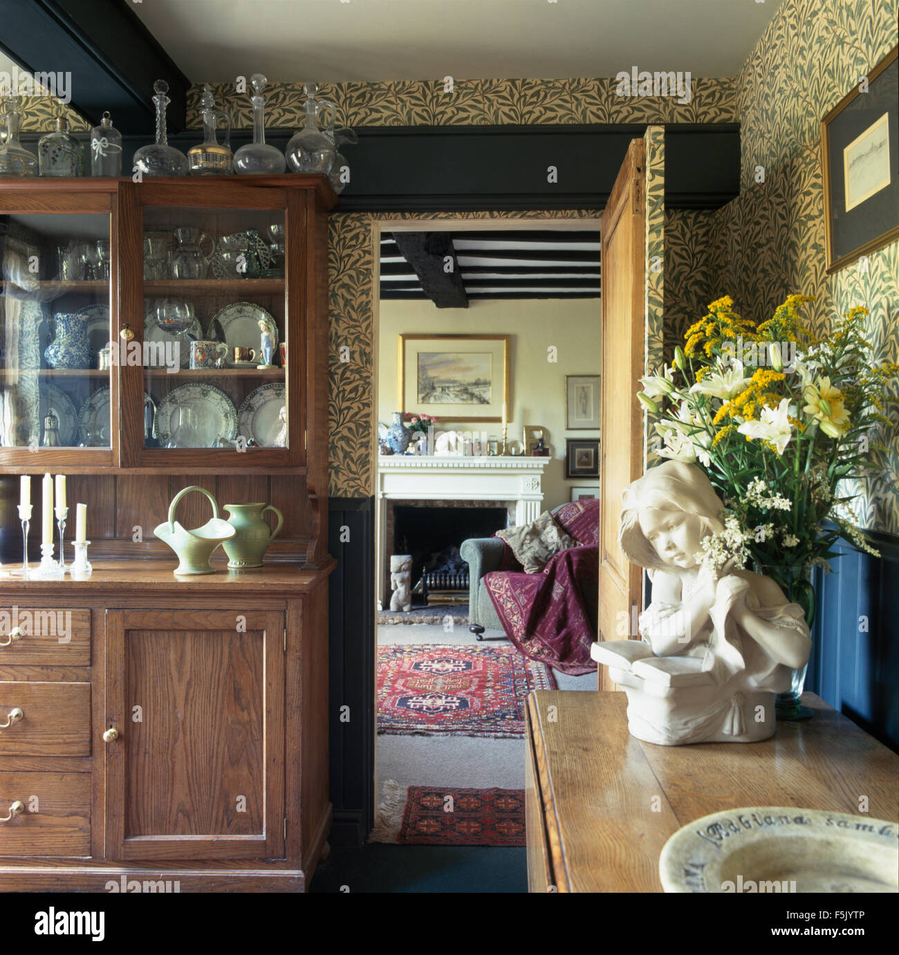 William Morris Green Willow Pattern Wallpaper In Old Fashioned Dining Room  With A Glass Front Dresser