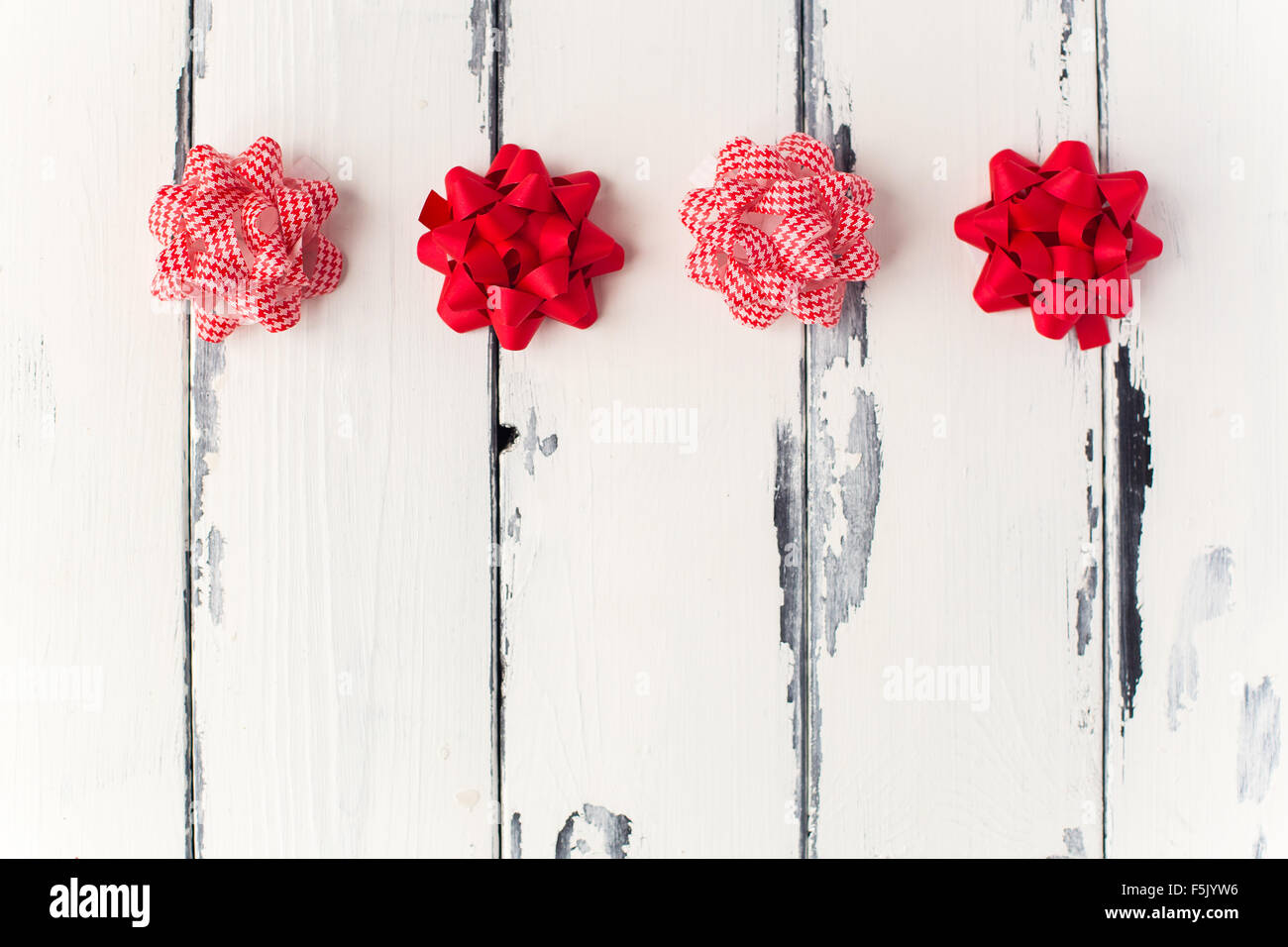 red bows on white wooden background - Stock Image