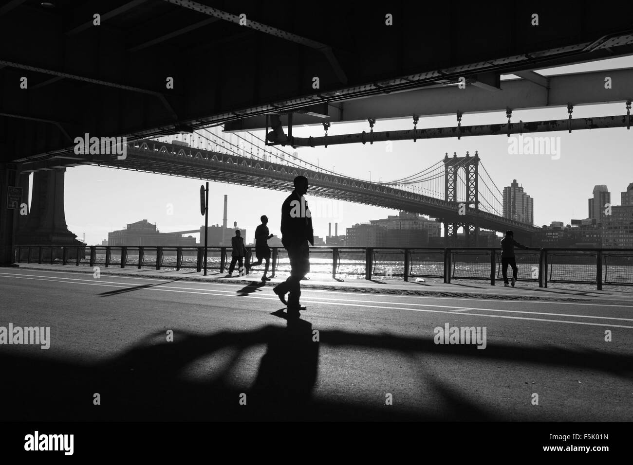 Two Chinatown women exercise, a man runs,  another man walks while watching the others along the East River Esplanade, - Stock Image