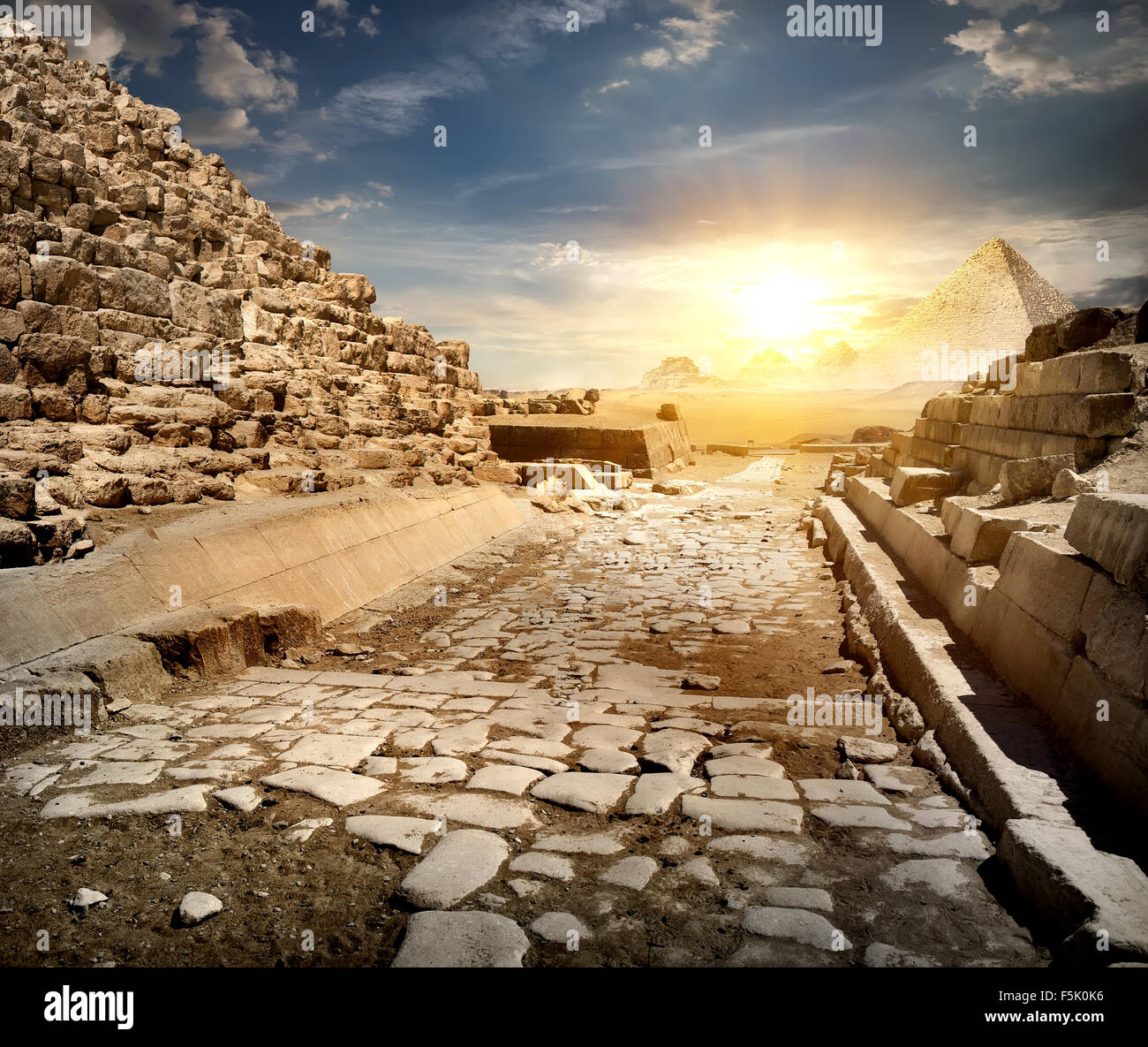 Way through ruins of egyptian pyramids and sun - Stock Image