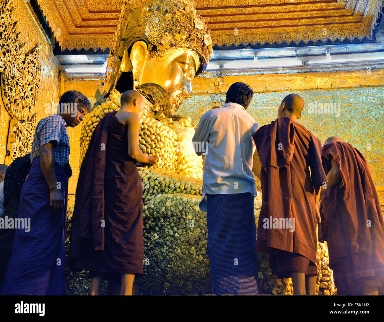 Monks applying gold leaf to the Mahamuni Buddha,Mandalay,Myanmar, (Burma) - Stock Image