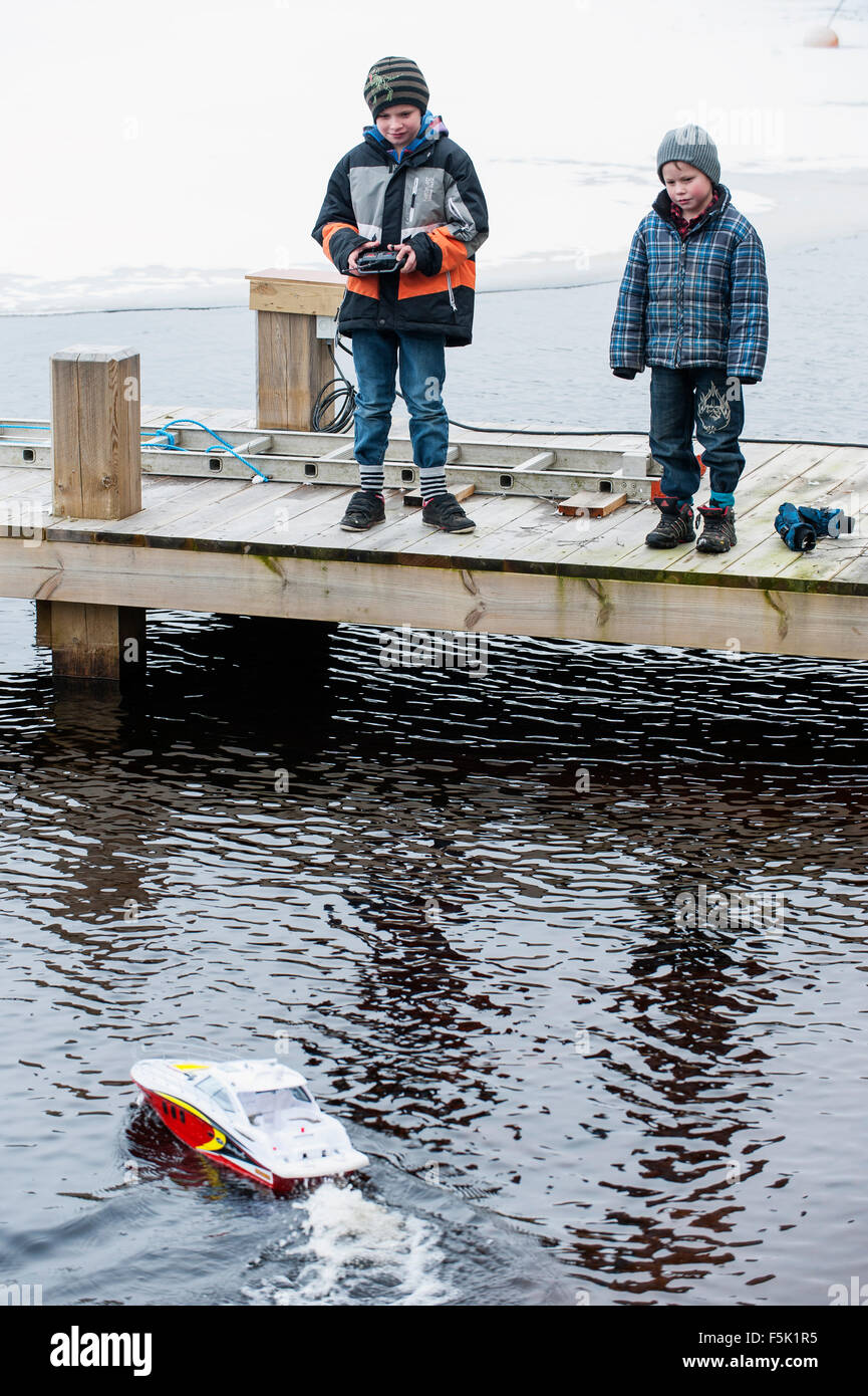 Boys and radio-controlled boat - Stock Image
