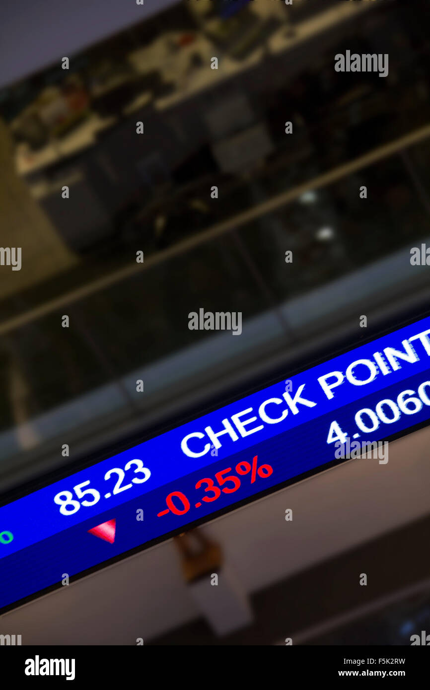 Display stock market charts on blue neon line with blurred office background - Stock Image