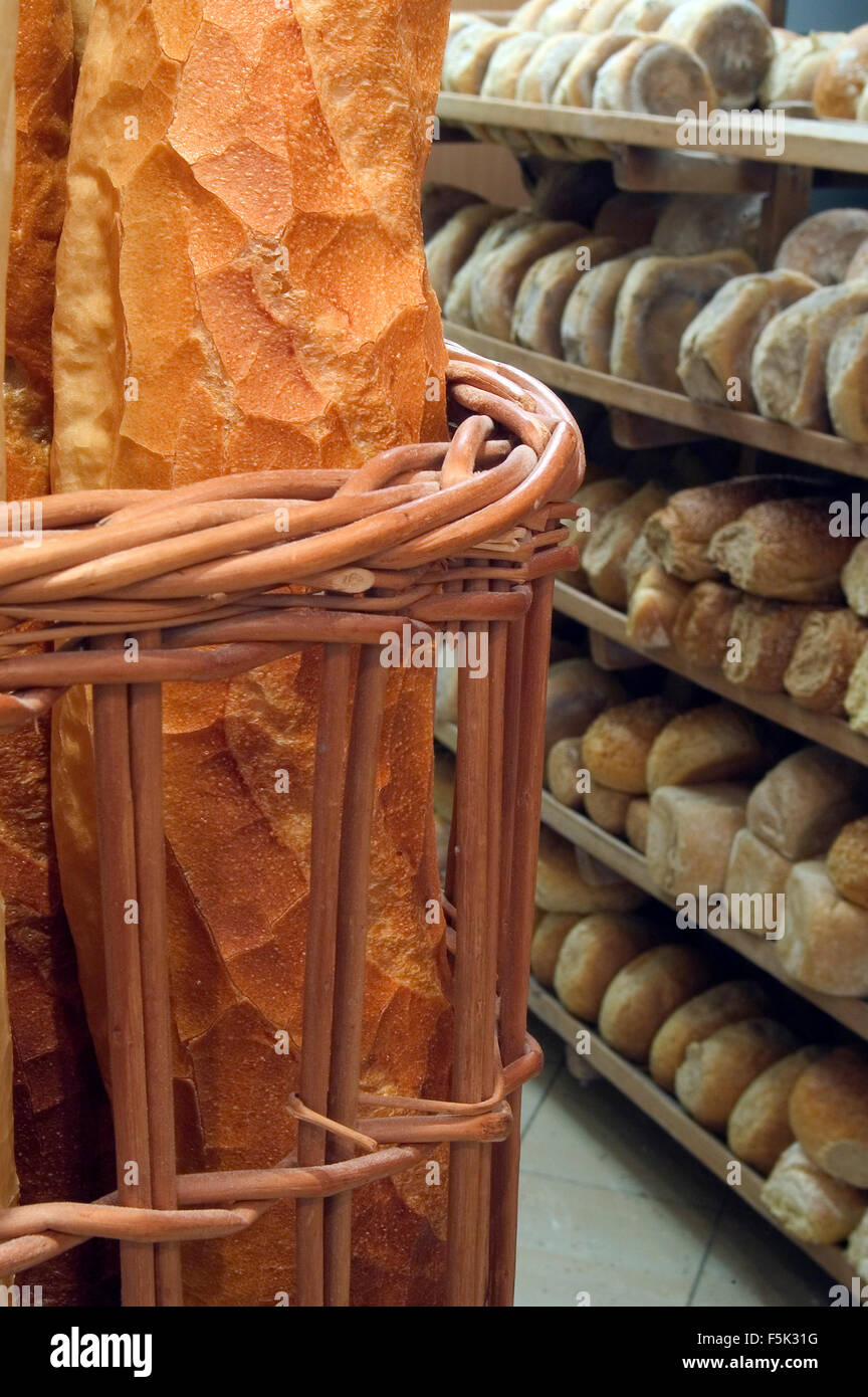Baguettes and shelves with loaves of fresh baked bread on display in bakery shop - Stock Image