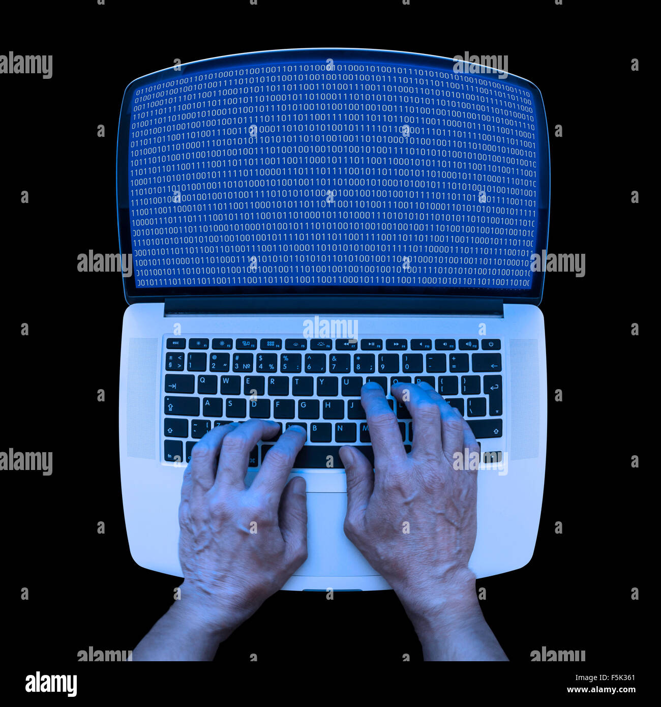 A developer in informatics is using a laptop to code in binary system at night - Stock Image