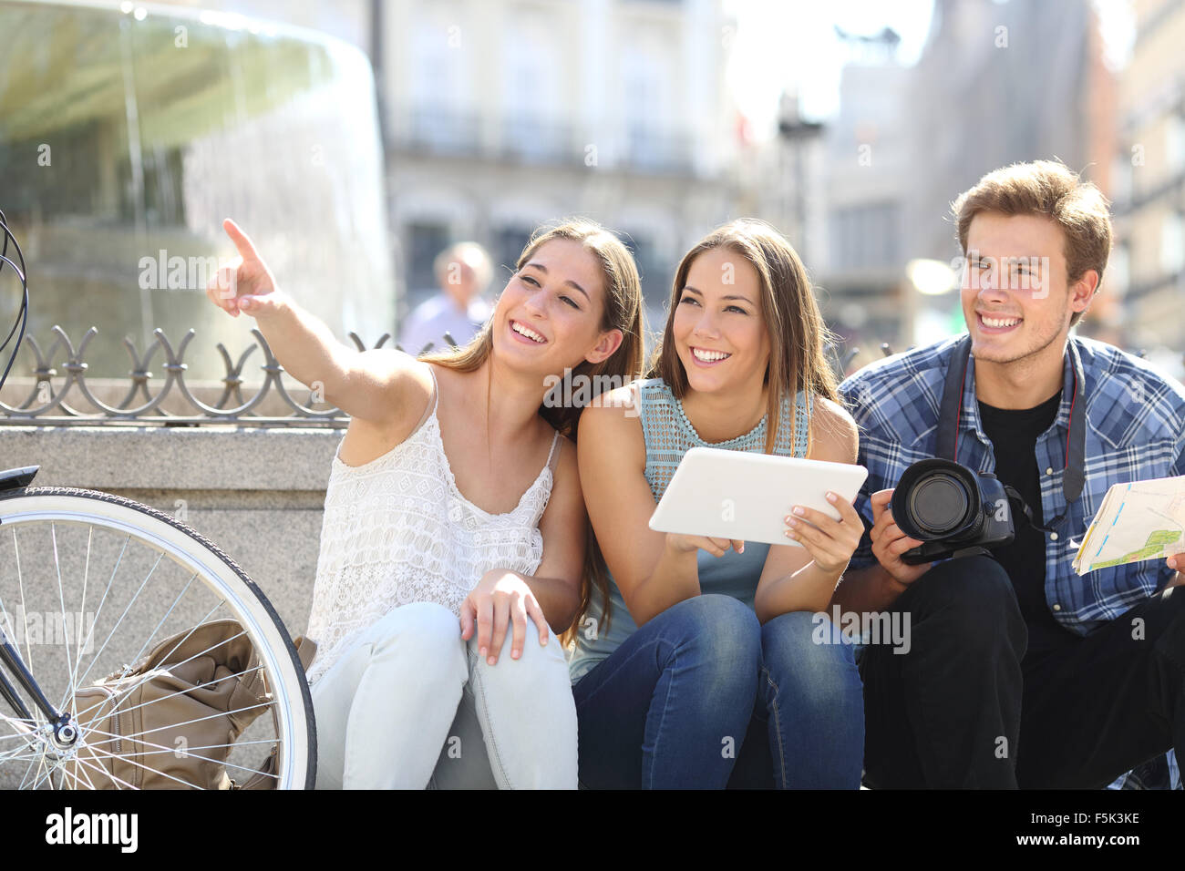 Tourist friends searching locations sightseeing in a city street - Stock Image