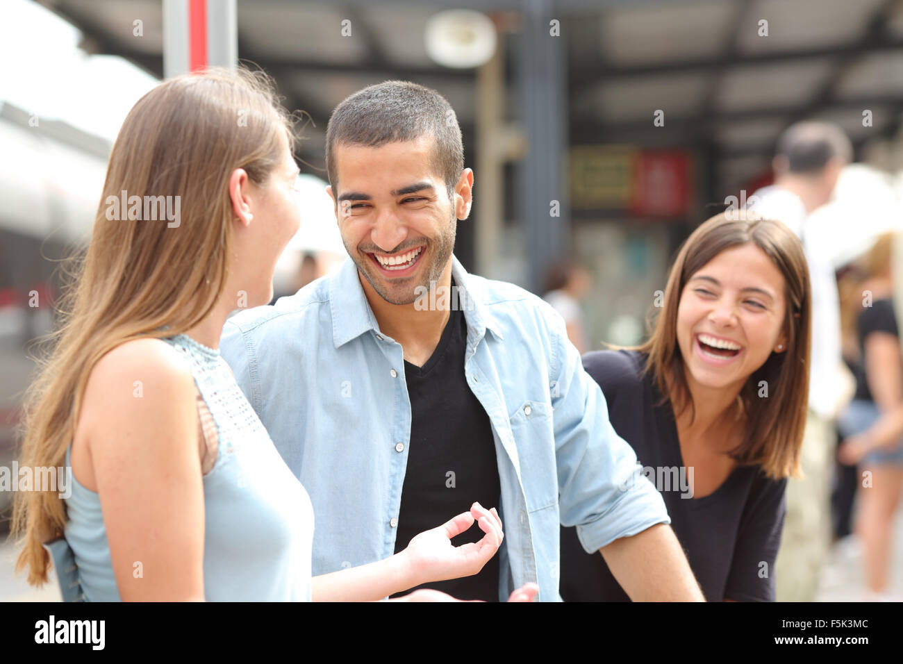 Three friends talking and laughing taking a conversation in a train station - Stock Image