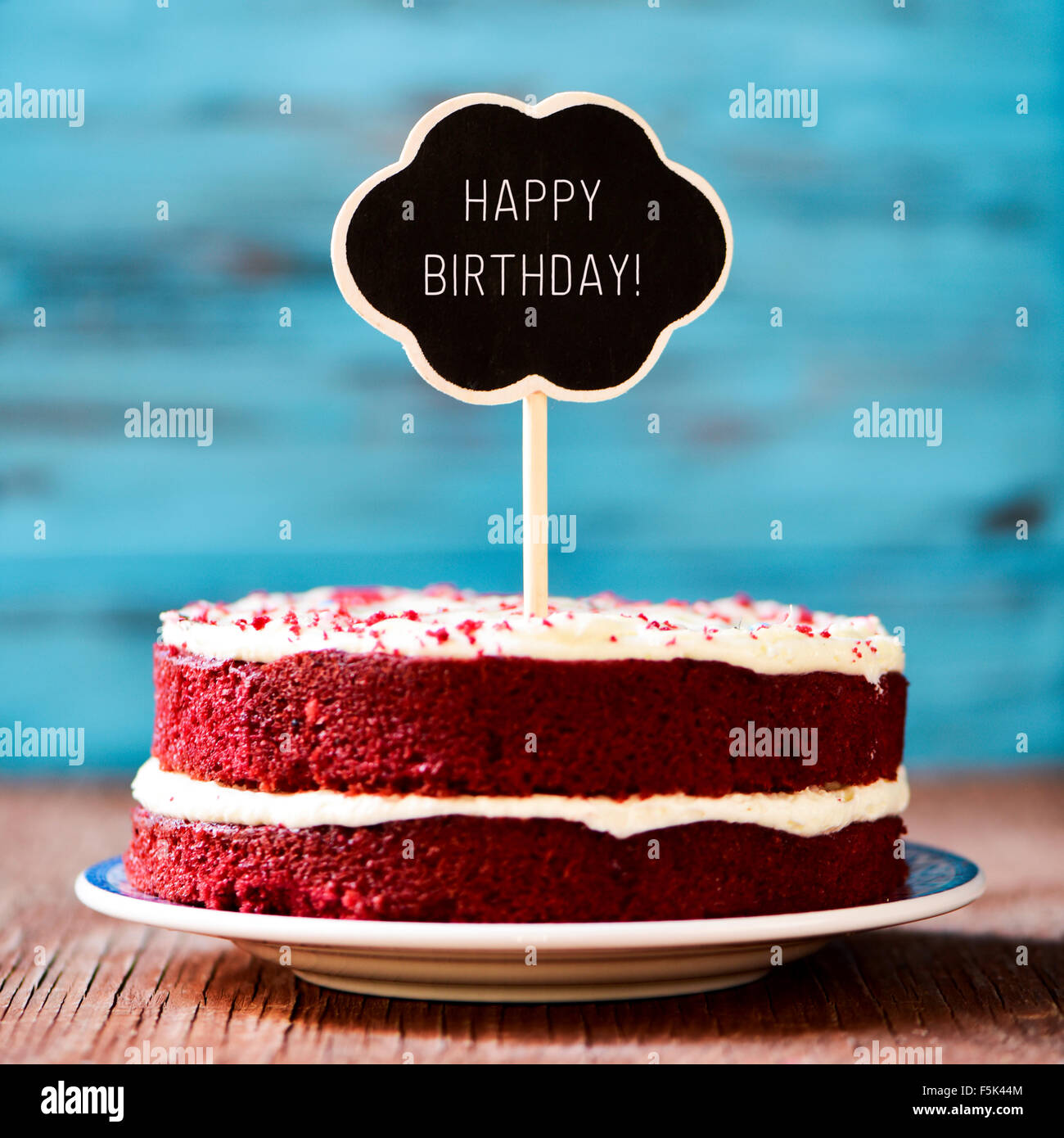 a red velvet cake with a chalkboard in the shape of a thought bubble with the text happy birthday, on a rustic wooden - Stock Image