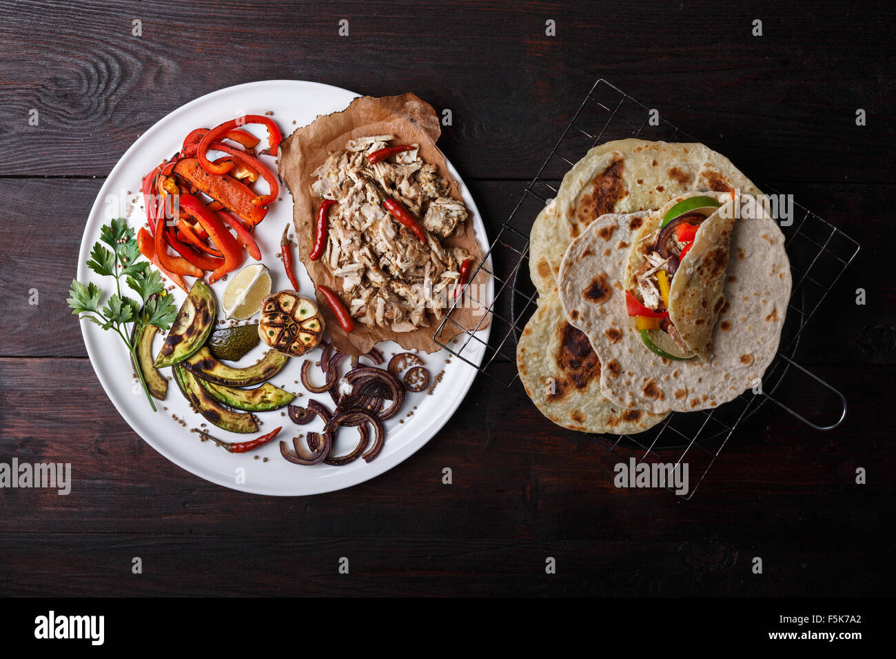 Fajita with pulled pork and bell peppers. Tortillas, grilled avocado, onions  served with meat and vegetables on - Stock Image