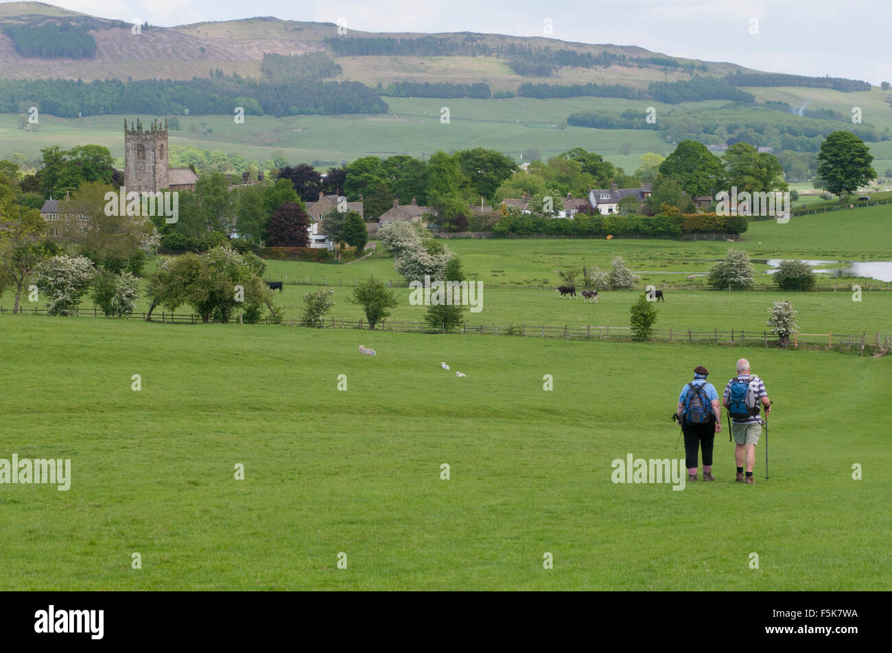 Couple of ramblers in beautiful countryside walking across a field towards rolling hills & scenic village of - Stock Image