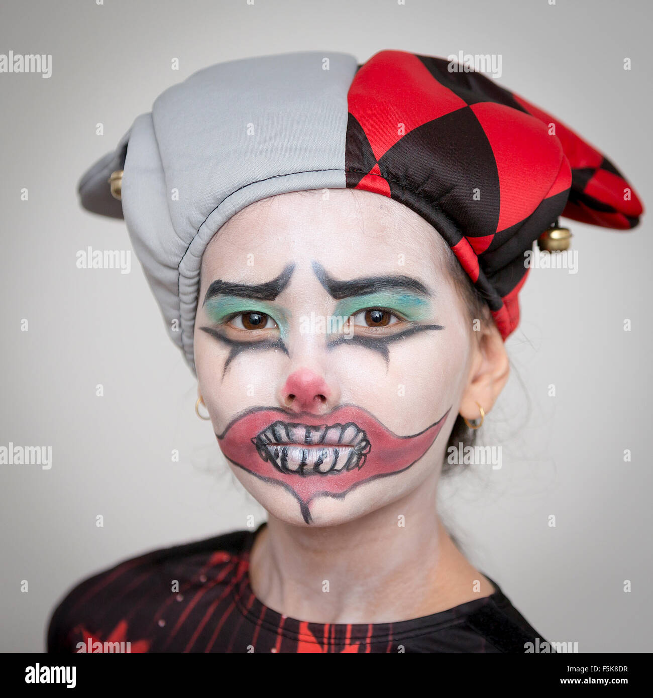 portrait of a young 10 year old british thai girl dressed for halloween with clown face paint